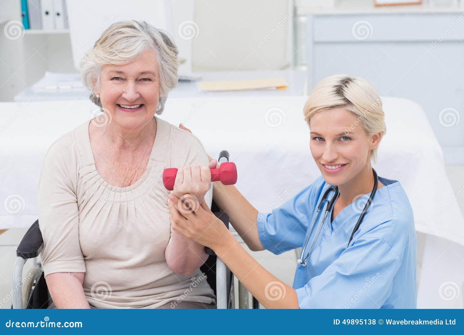 Infermiere che assiste paziente femminile nella testa di legno di sollevamento