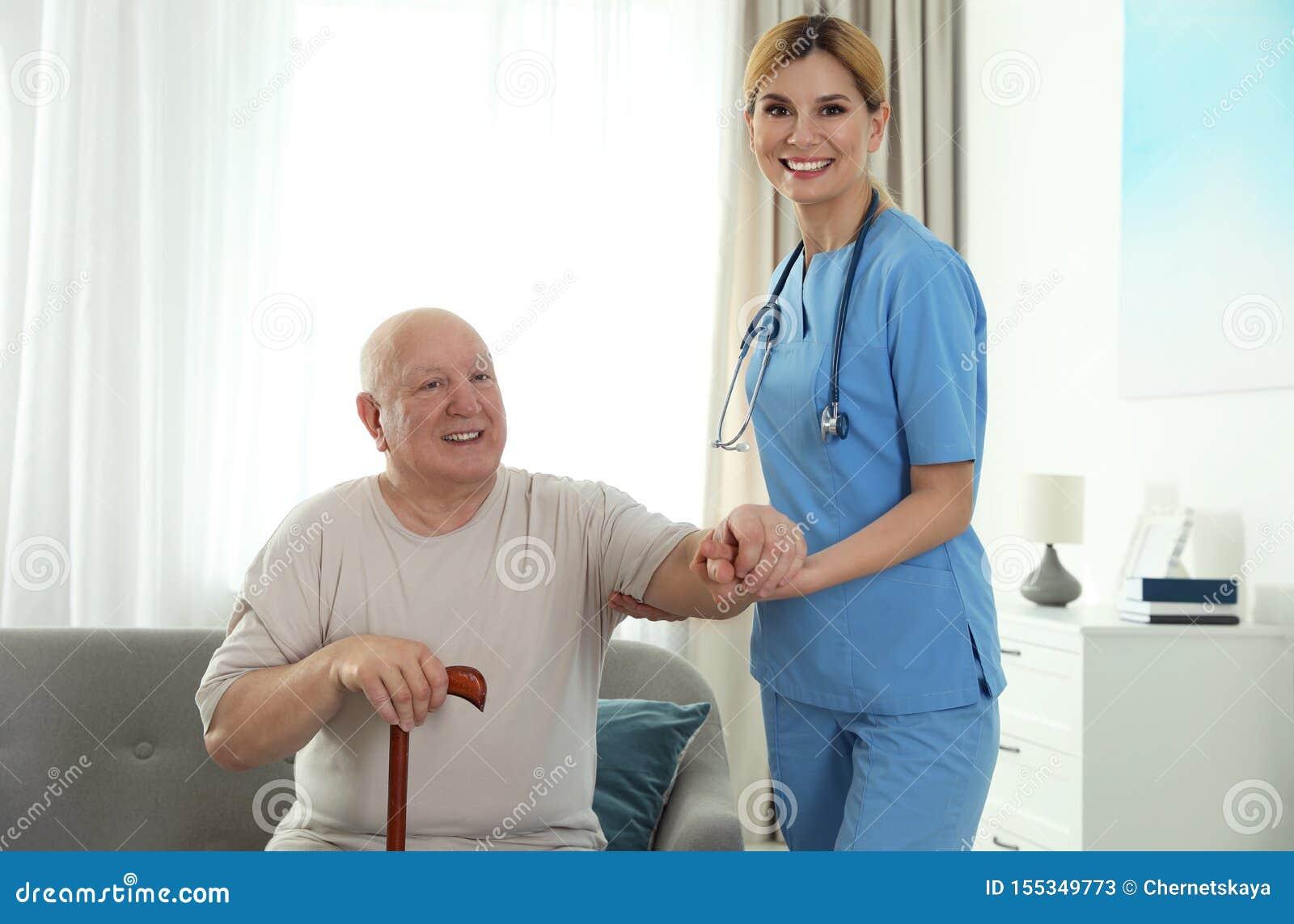 Infermiere che assiste uomo anziano con la canna