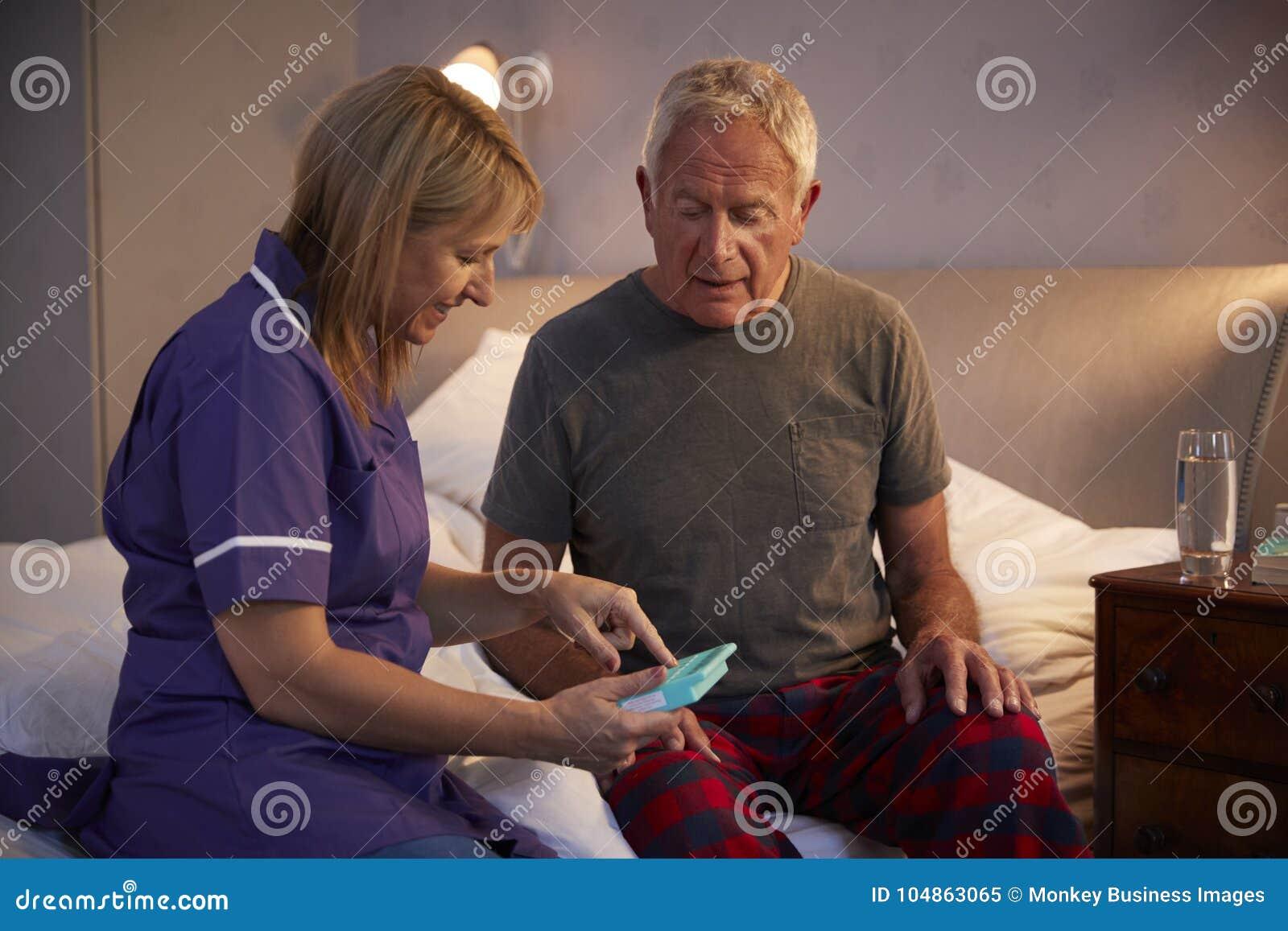 Infermiere Helping Senior Man per organizzare farmaco sulla visita domestica