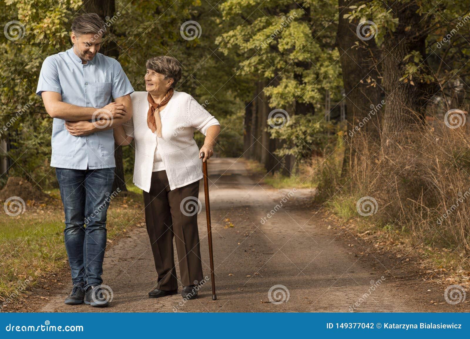 Infermiere maschio che sostiene donna felice con il bastone da passeggio nella foresta