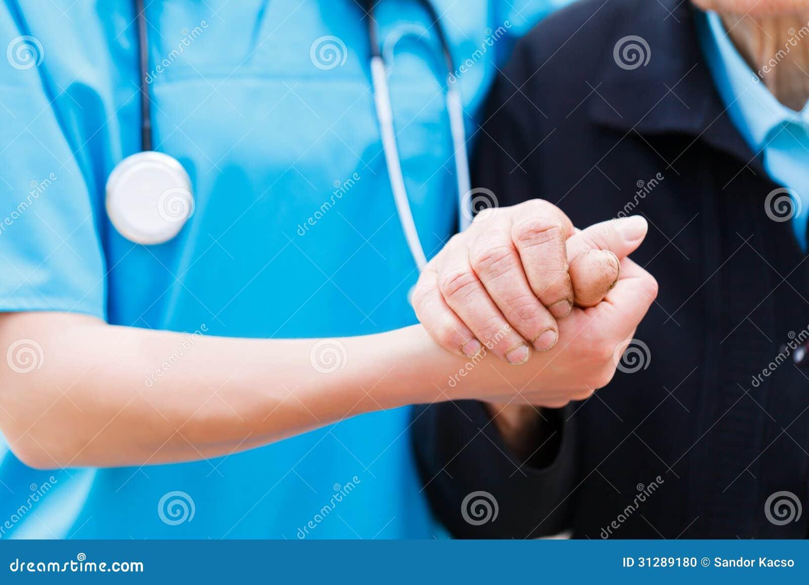 Infermiere preoccupantesi che tiene le mani anziane