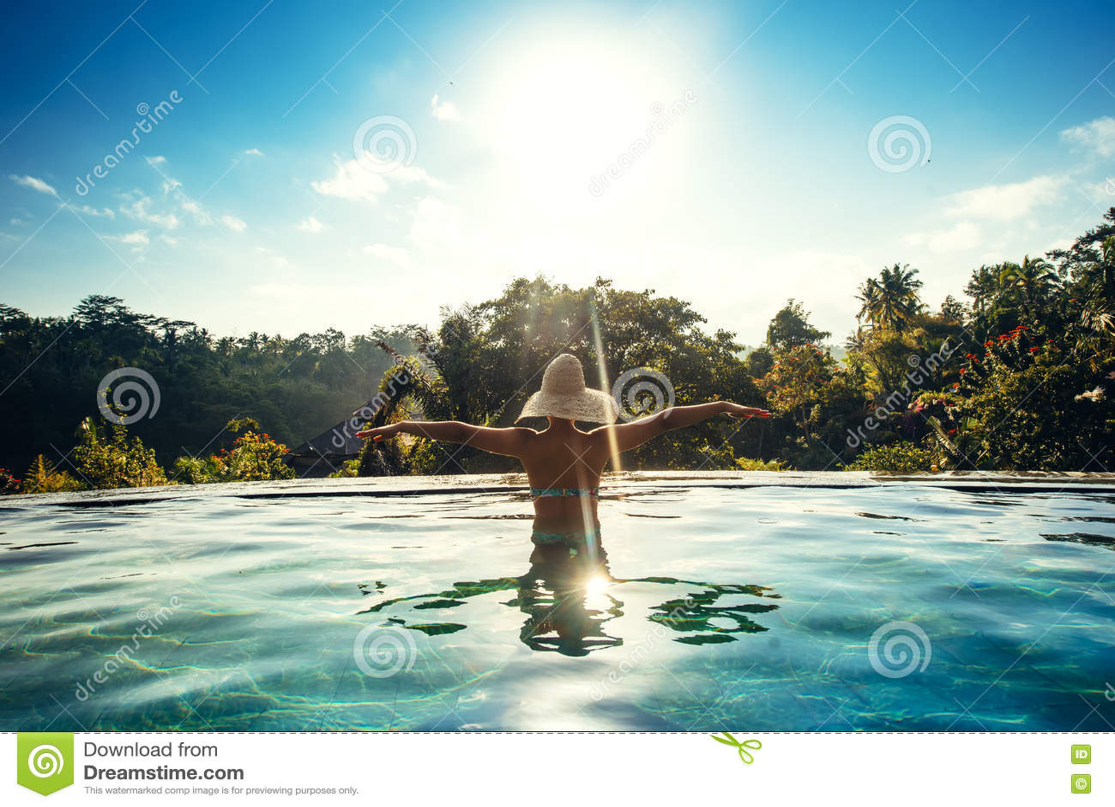Infinity pool on luxurious exotic island. Portrait of girl wearing hat enjoying the sun at pool