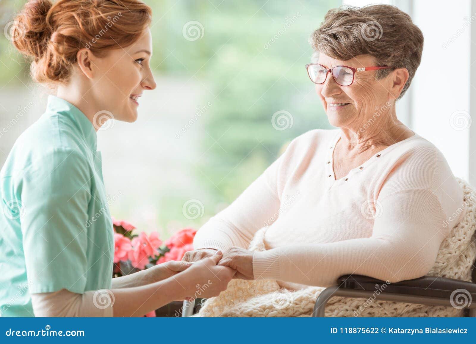 Infirmière compatissante expliquant un patient handicapé gériatrique W