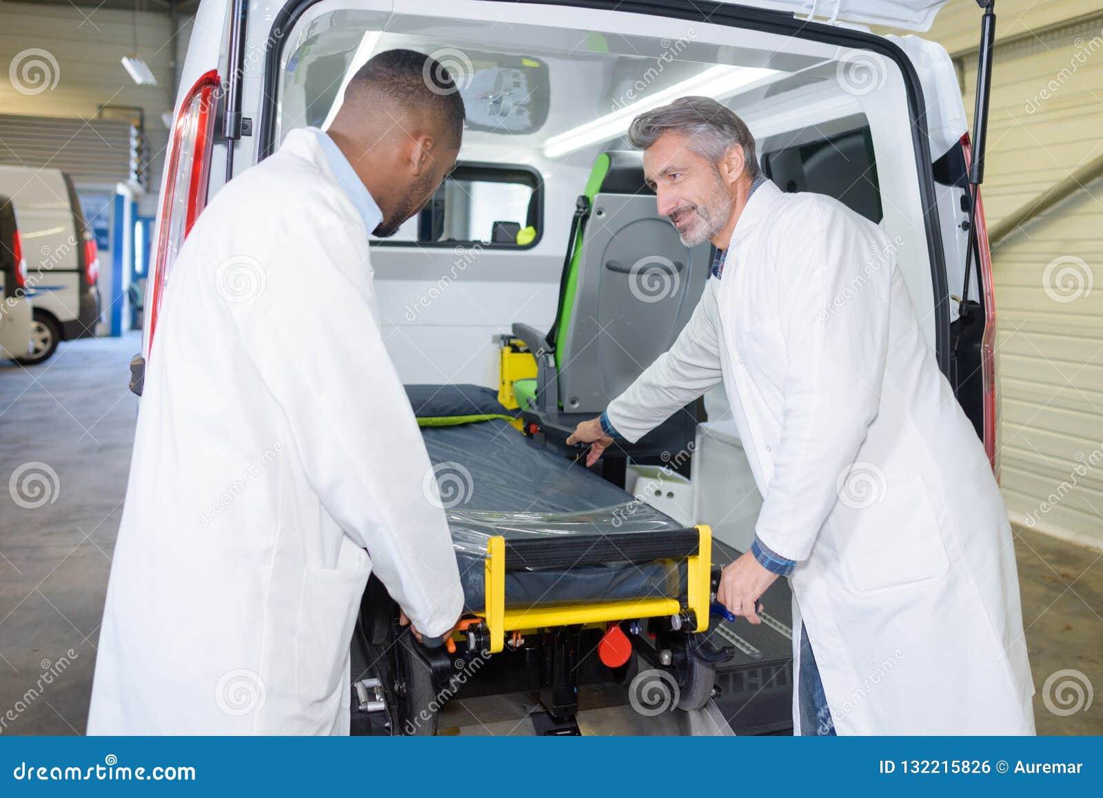 Infirmiers chargeant la civière dans l ambulance