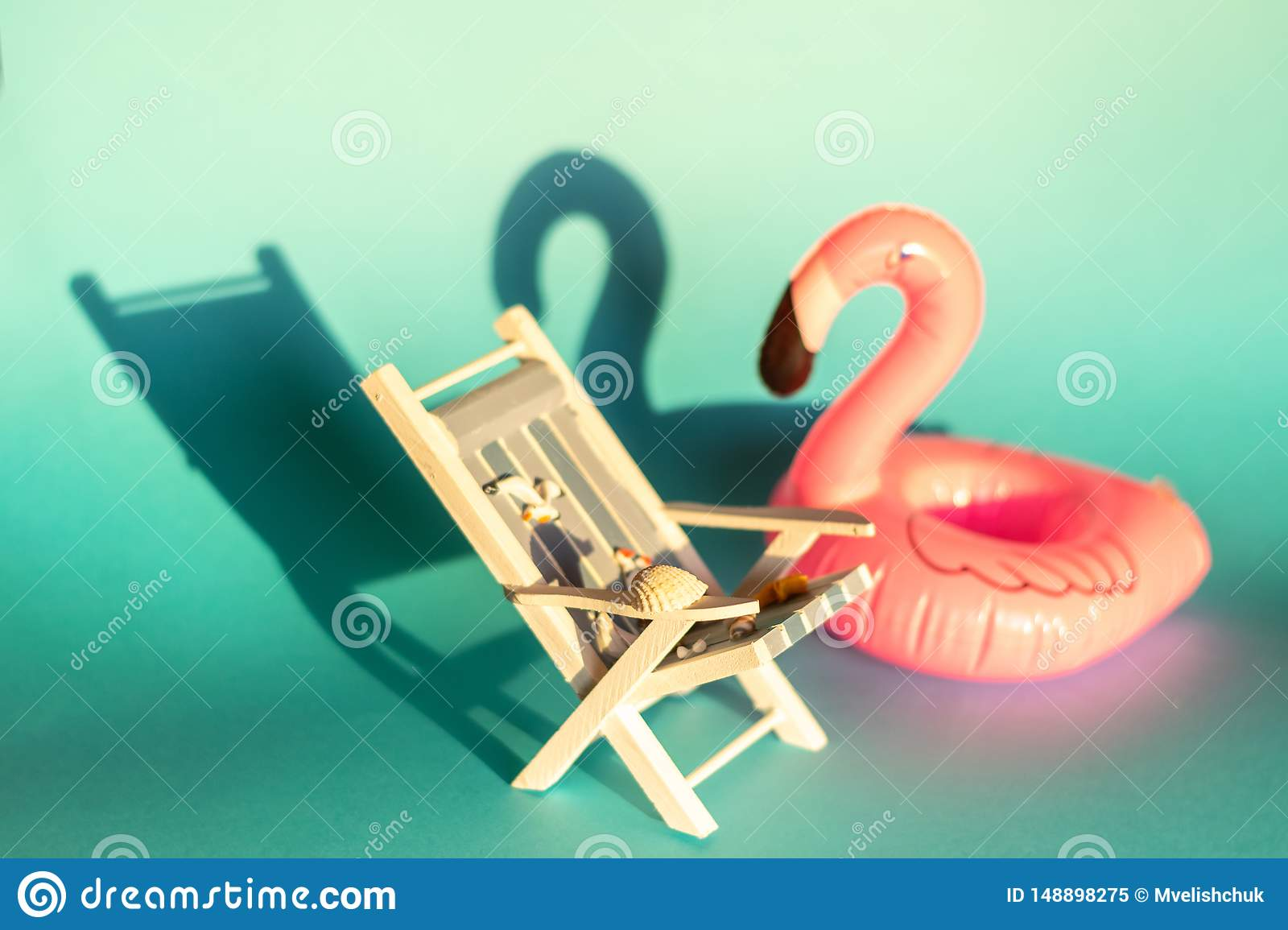 Inflatable Flamingo and deckchair on a blue background, pool float party,