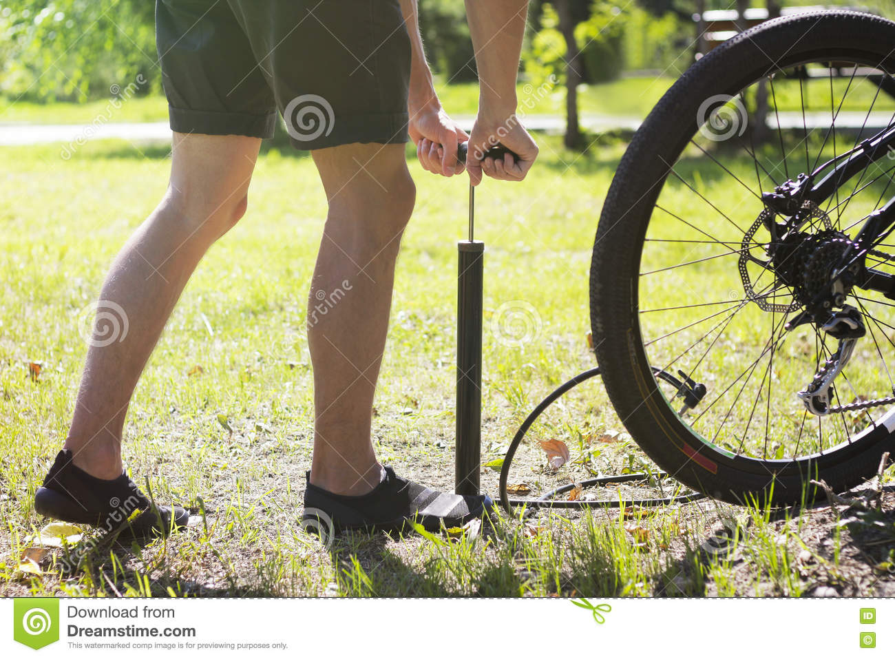Inflating The Tire Of A Bicycle. Cyclist Repairs Bike In ...