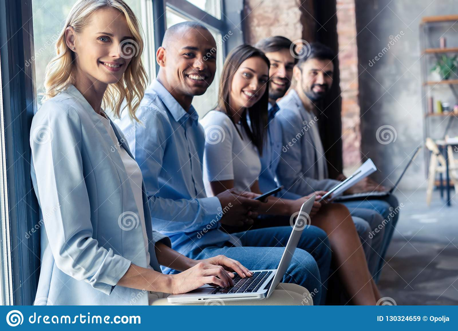 Informação realmente boa Grupo de jovens que sentam-se na conferência junto e no sorriso
