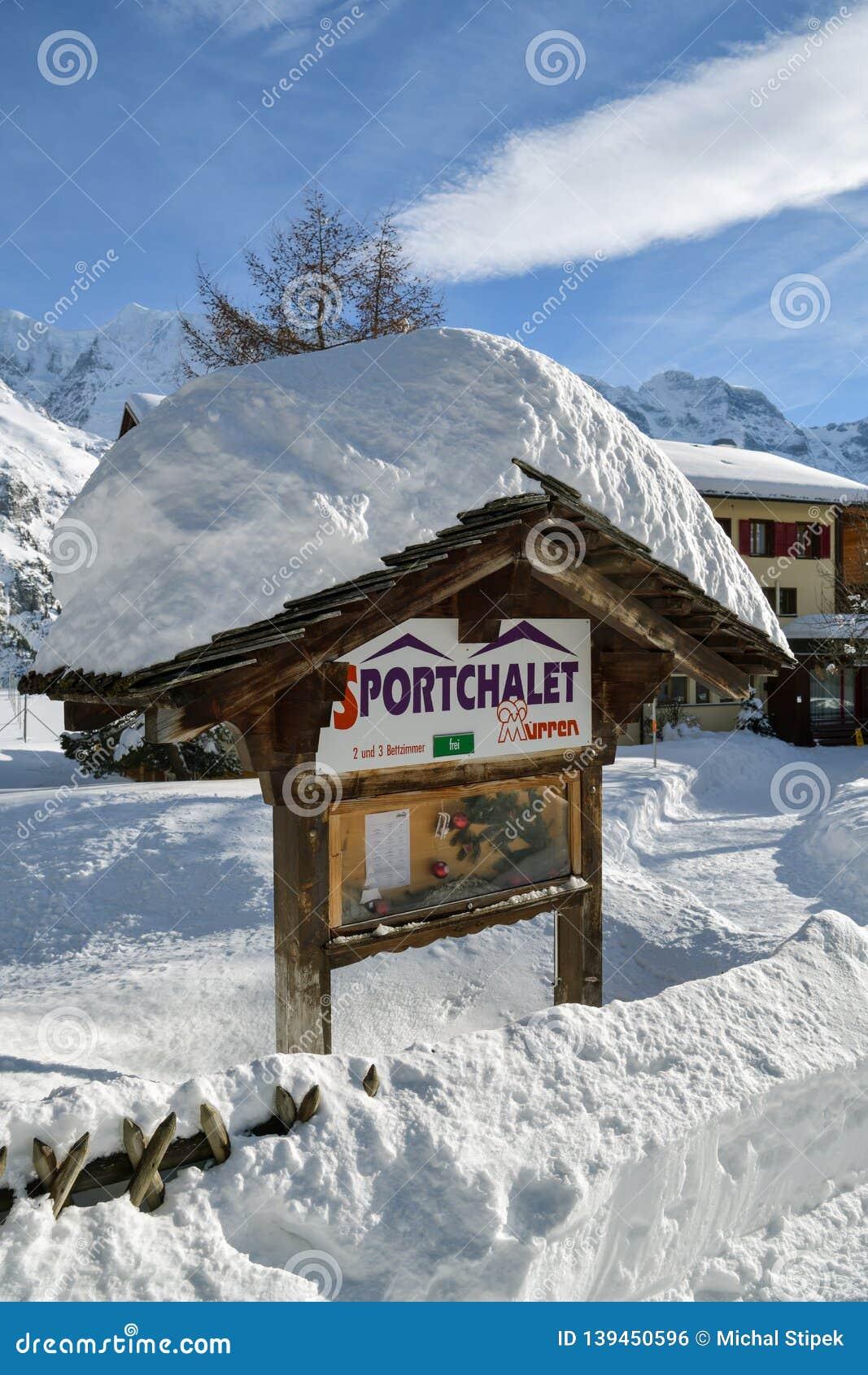 Informacji deska zakrywająca gęstą warstwą śnieg w górskiej wiosce Murren