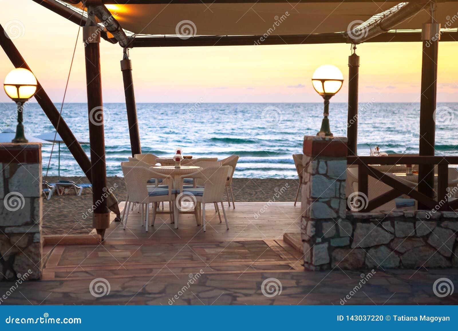 Ingång som tömmer kafét på den sandiga stranden på solnedgången Begrepp av loppet och semestern Sammetsäsong