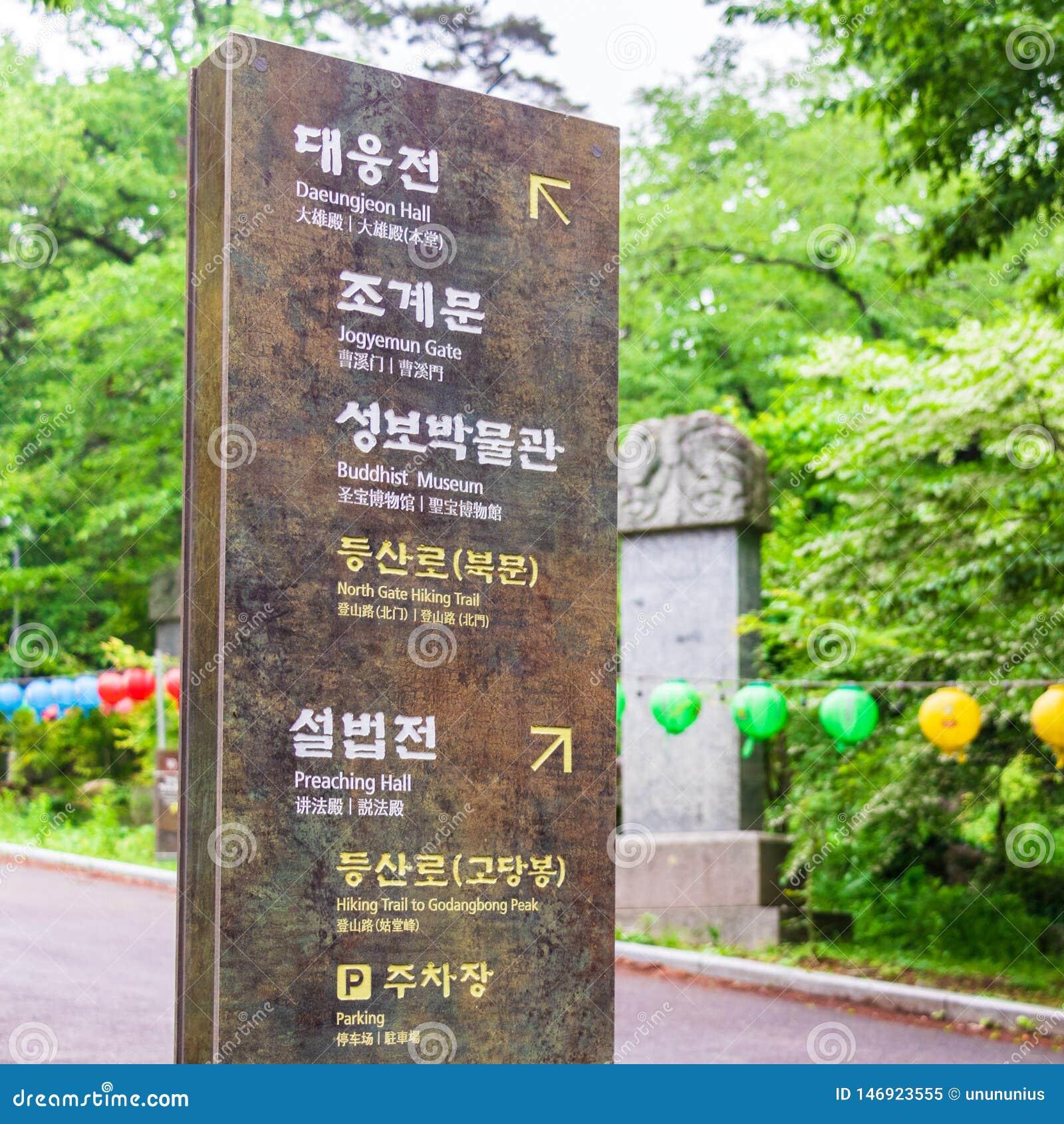 Ingångsbana med tecknet till den koreanska buddistiska templet Beomeosa på en dimmig dag Lokaliserat i Geumjeong, Busan, Sydkorea