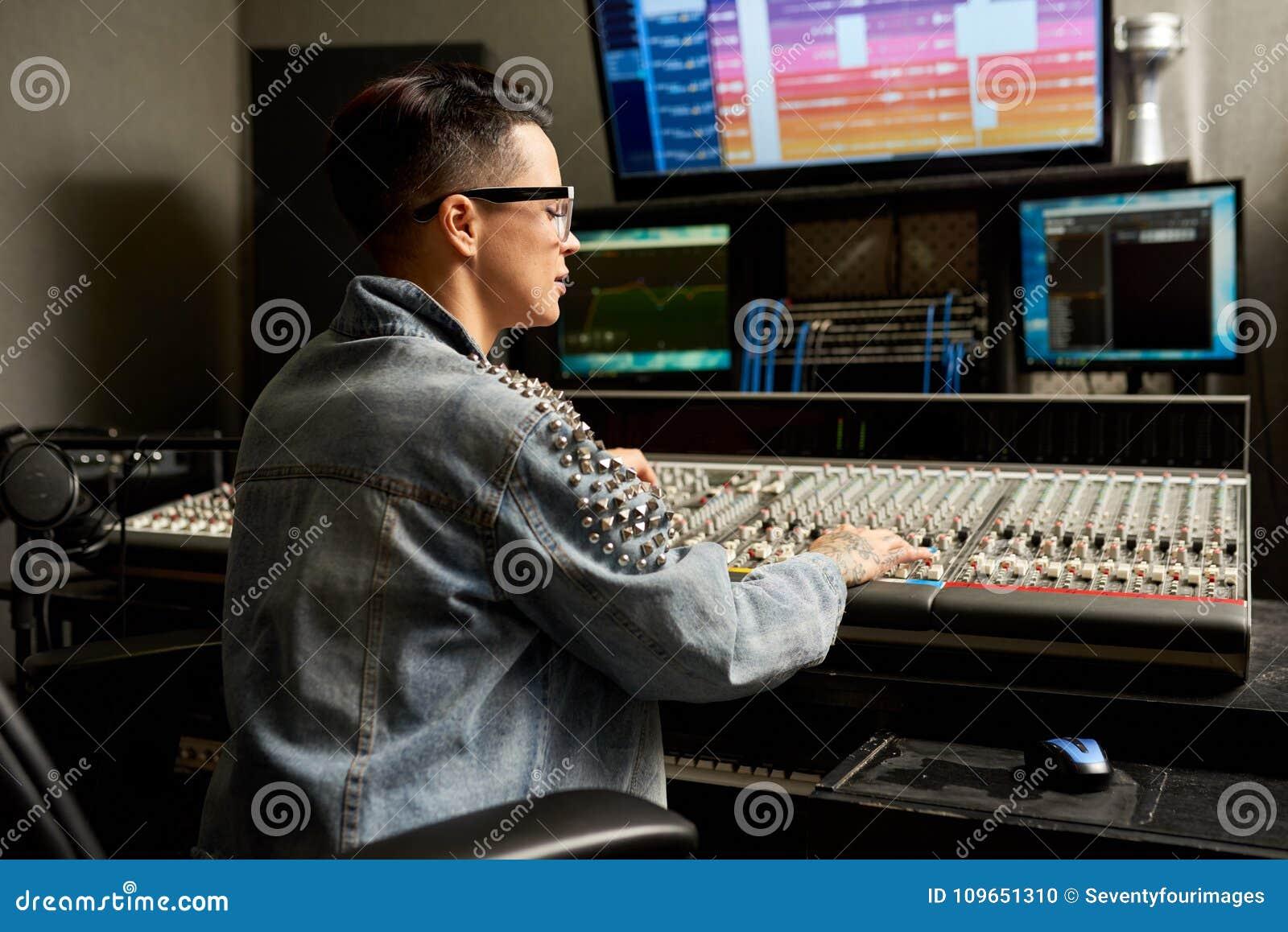 Ingénieur audio concentré ajustant le mélangeur dans le studio