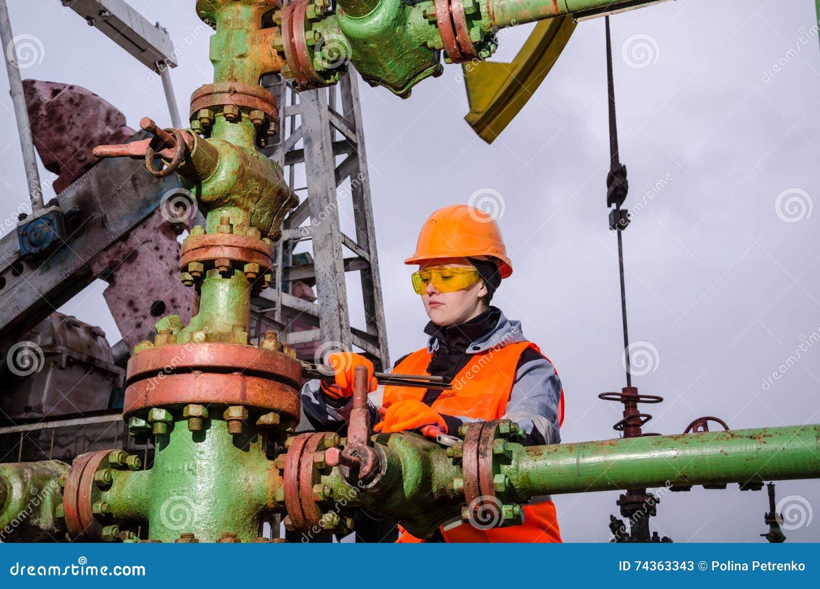 Ingénieur de femme dans le gisement de pétrole réparant la tête de puits