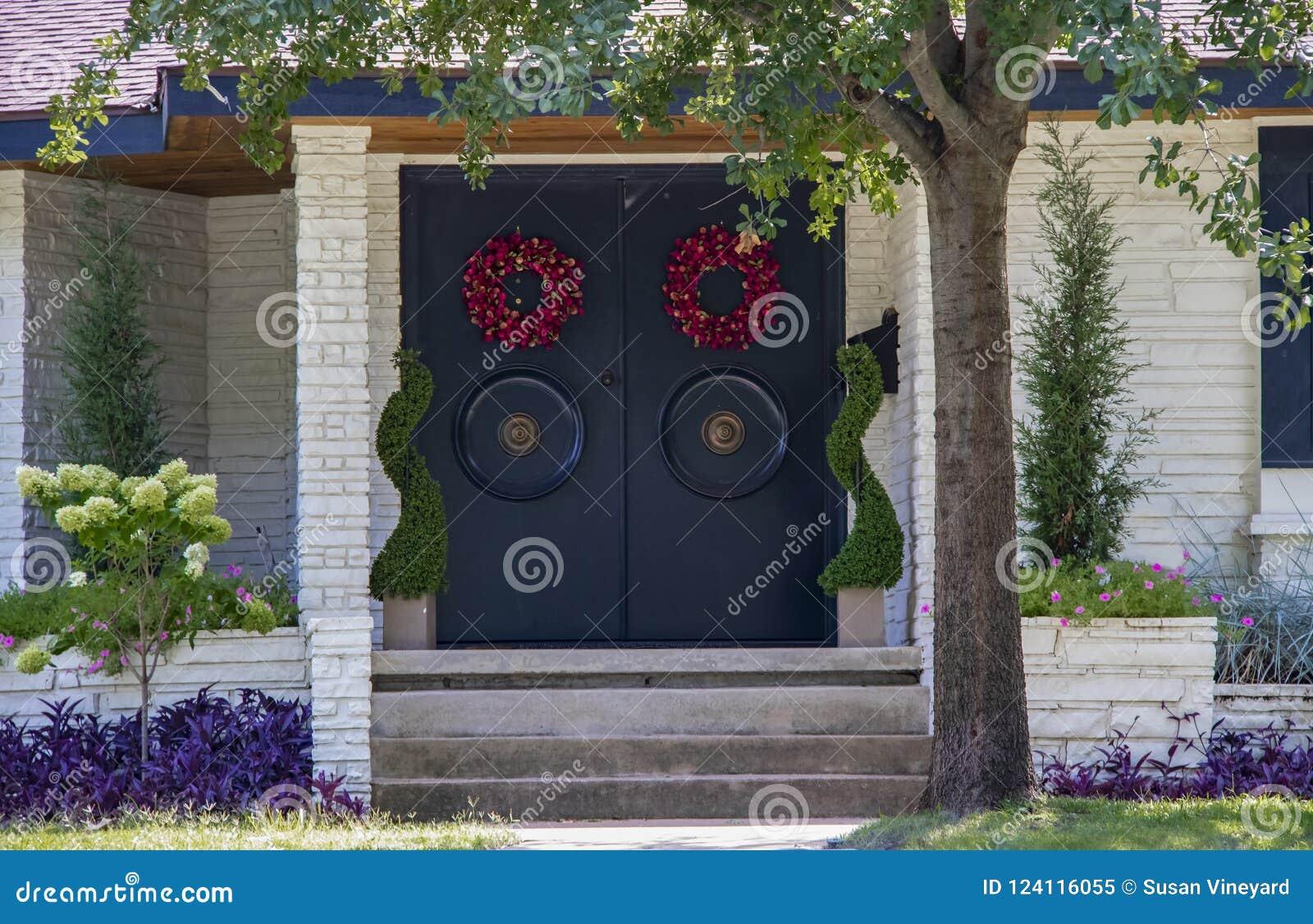 Ingang van een wit steenhuis voor de betere inkomstklasse met Aziatische stijldeuren met grote ronde handvatten en rode kronen en