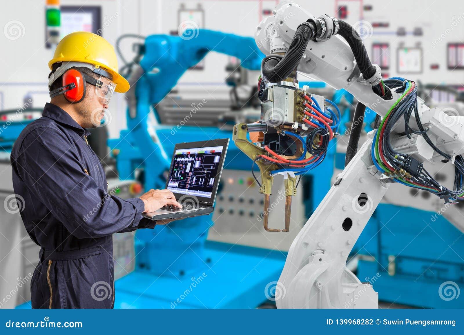 Ingegnere facendo uso della macchina utensile robot automatica della mano di manutenzione del computer portatile nell industria a