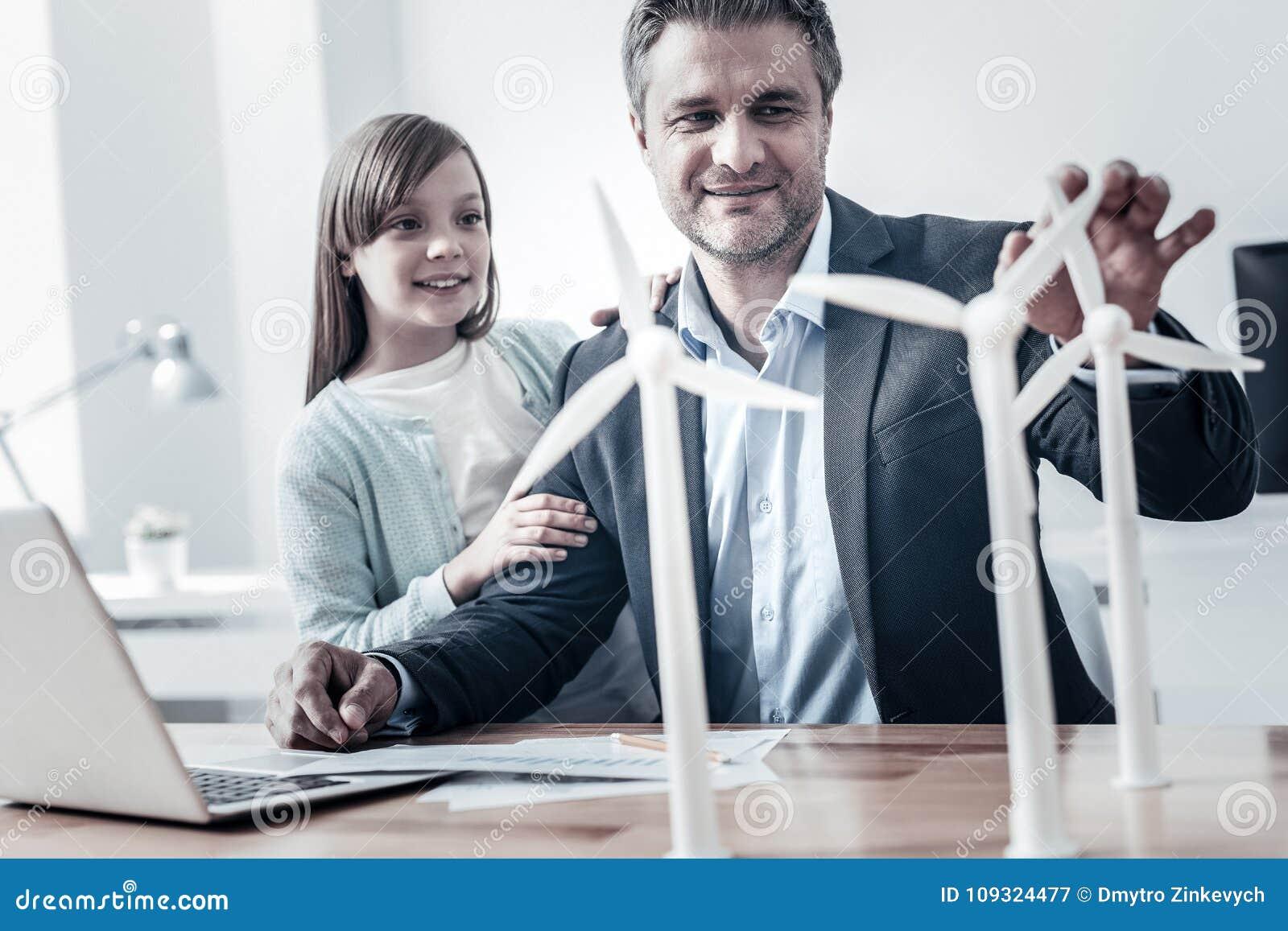 Ingeniero alegre que dice a su hija sobre energía alternativa