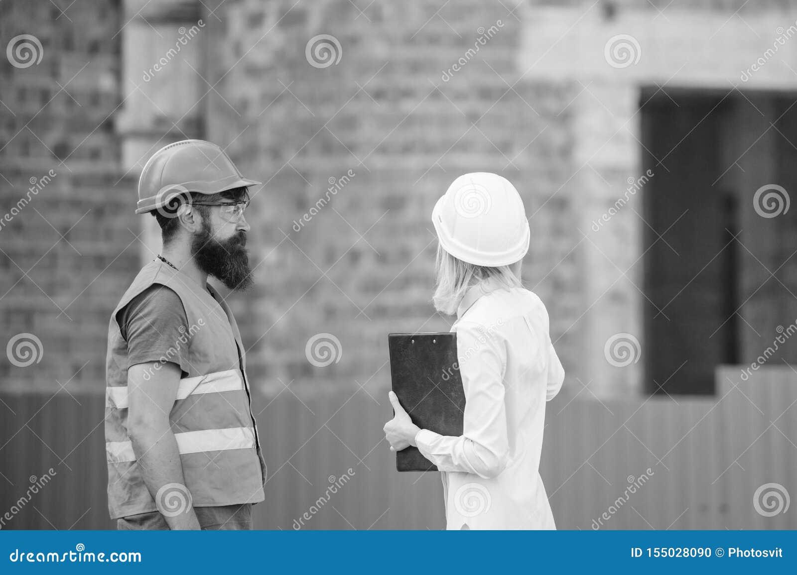Ingeniero de la mujer y constructor brutal barbudo discutir progreso de la construcci?n Discuta el plan del progreso Sector de la