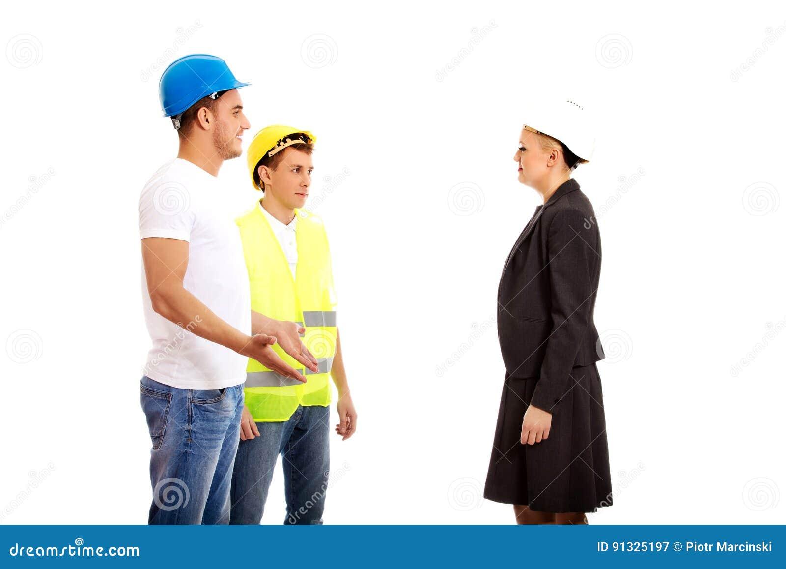 Ingeniero de sexo femenino que habla con dos constructores