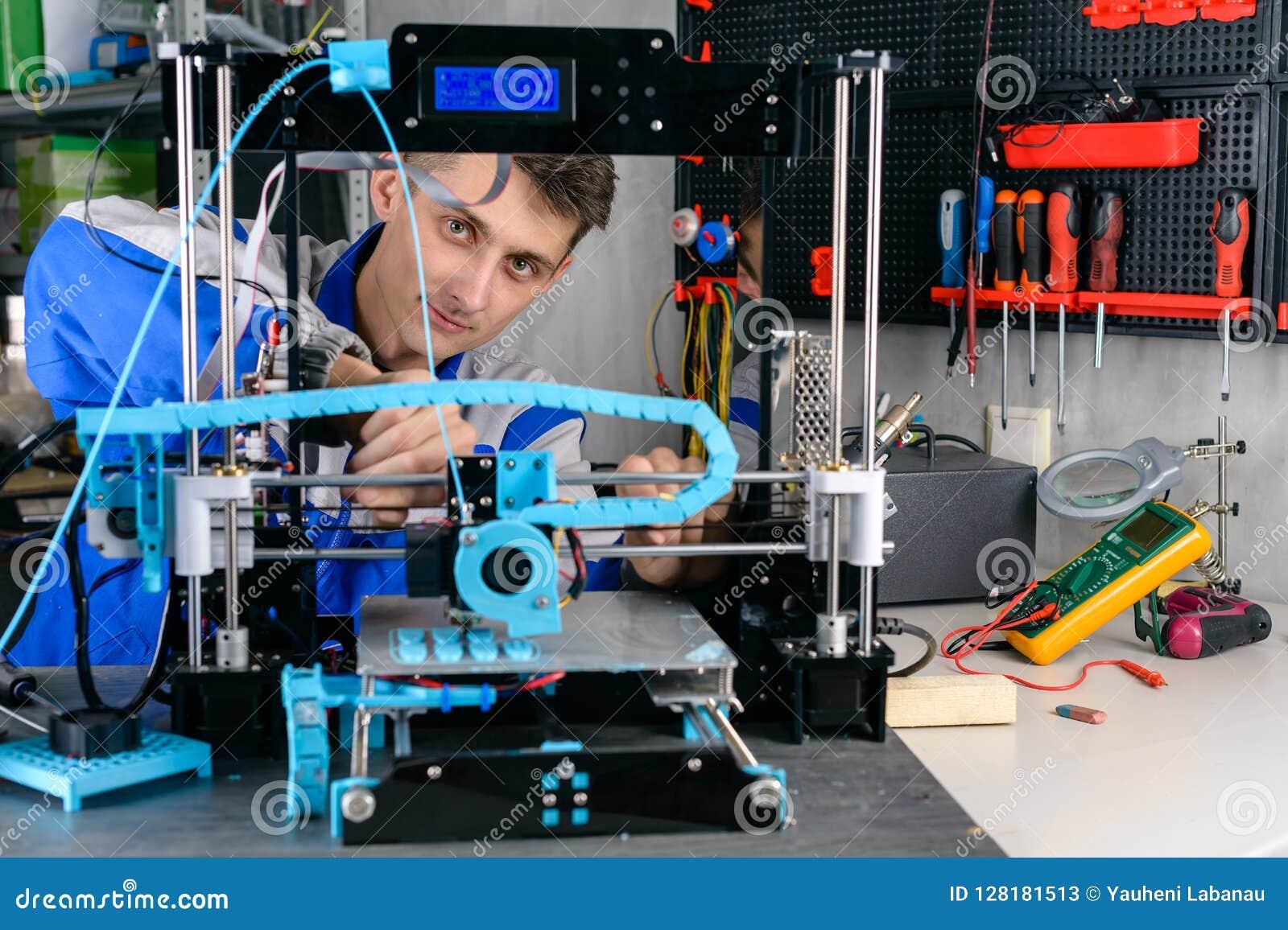 Ingeniero joven del diseñador usando una impresora 3D en laboratorio