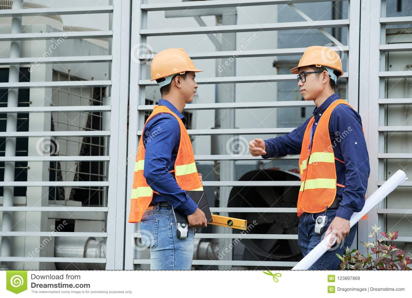 Ingenieros asiáticos que hablan cerca de la pared