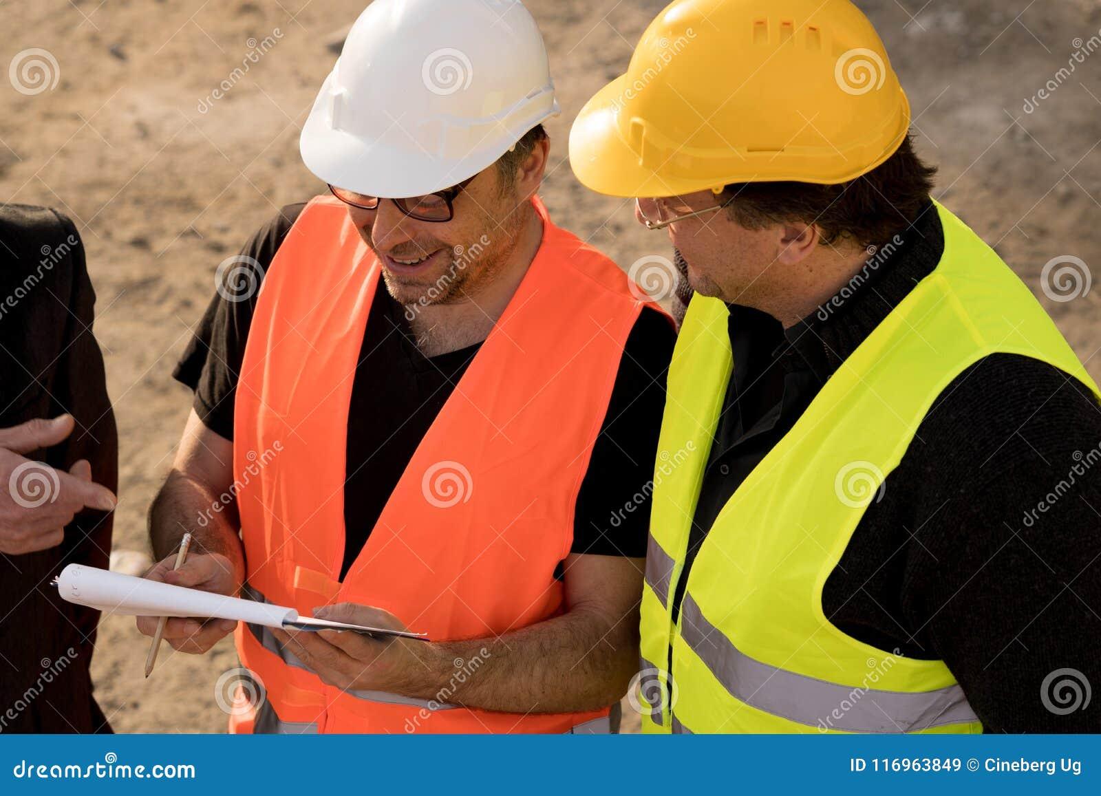 Ingenieros civiles que escriben en un cuaderno