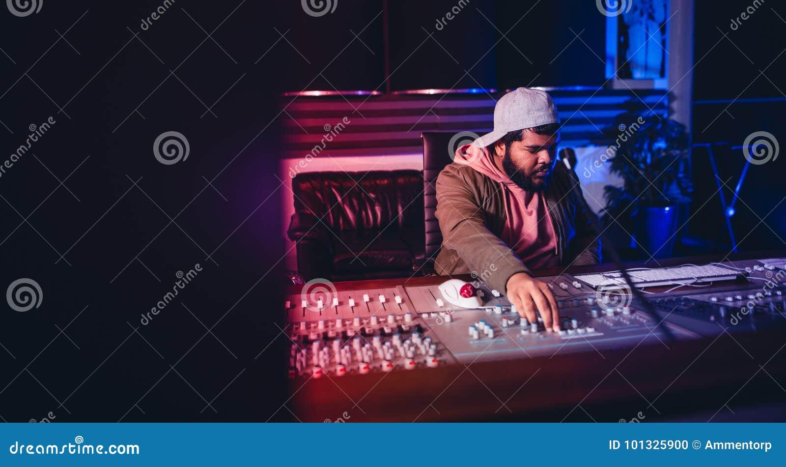 Ingenieur die aan geluid werken die bureau in opnamestudio mengen