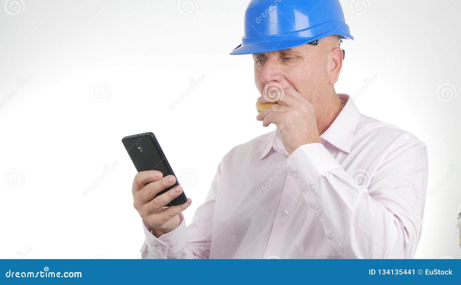 Ingenieur Image Eating ein Sandwich und ein Text unter Verwendung des Handys