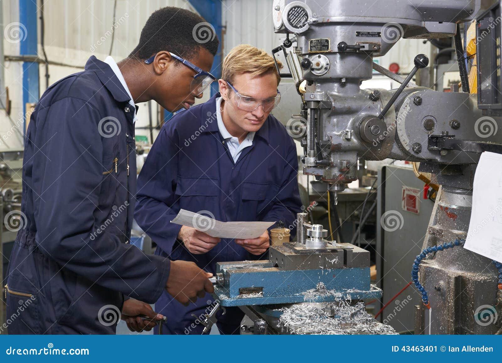 Ingenieur Showing Apprentice How aan Gebruiksboor in Fabriek