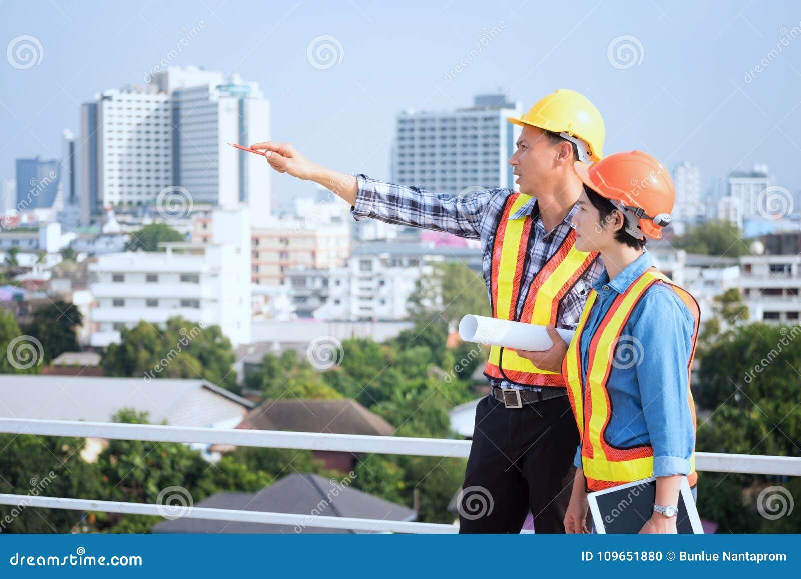 Ingenieure sind, schauend zu Hause treffend, bearbeitend und Plan herein