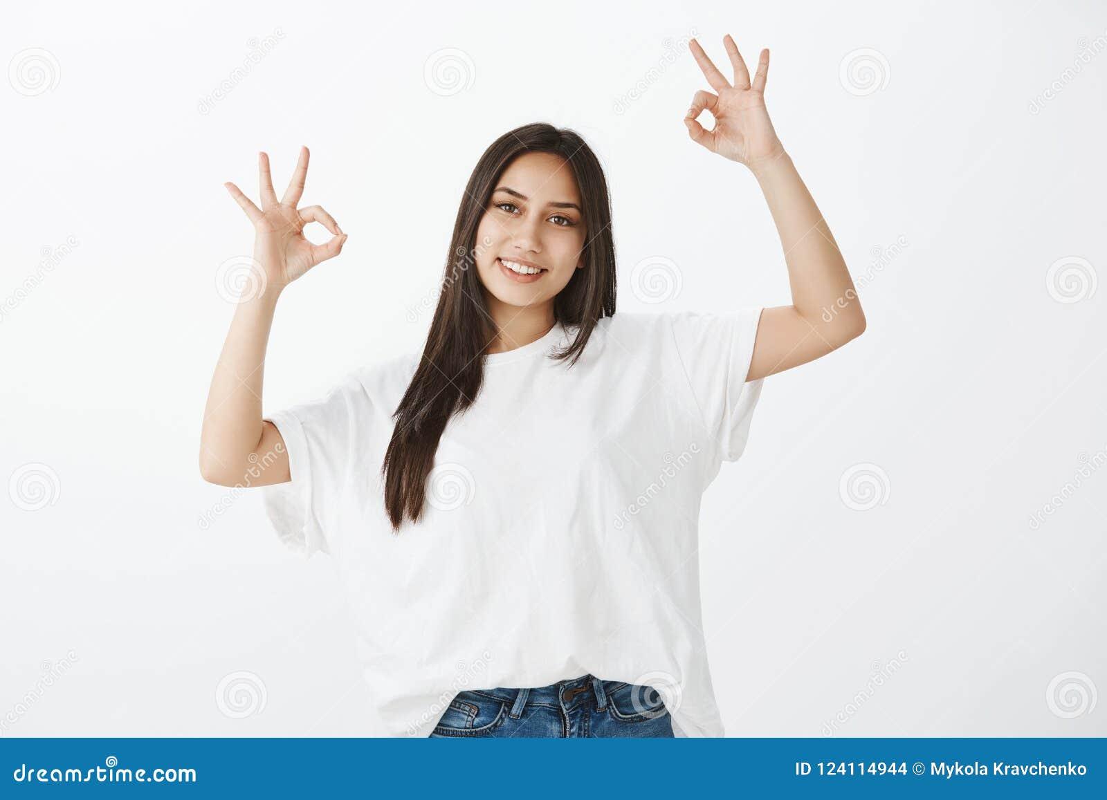 Inget bekymrat, allt ok Stående av realiteten som grinar den kvinnliga studenten i den vita t-skjortan som lyfter händer i ok ell