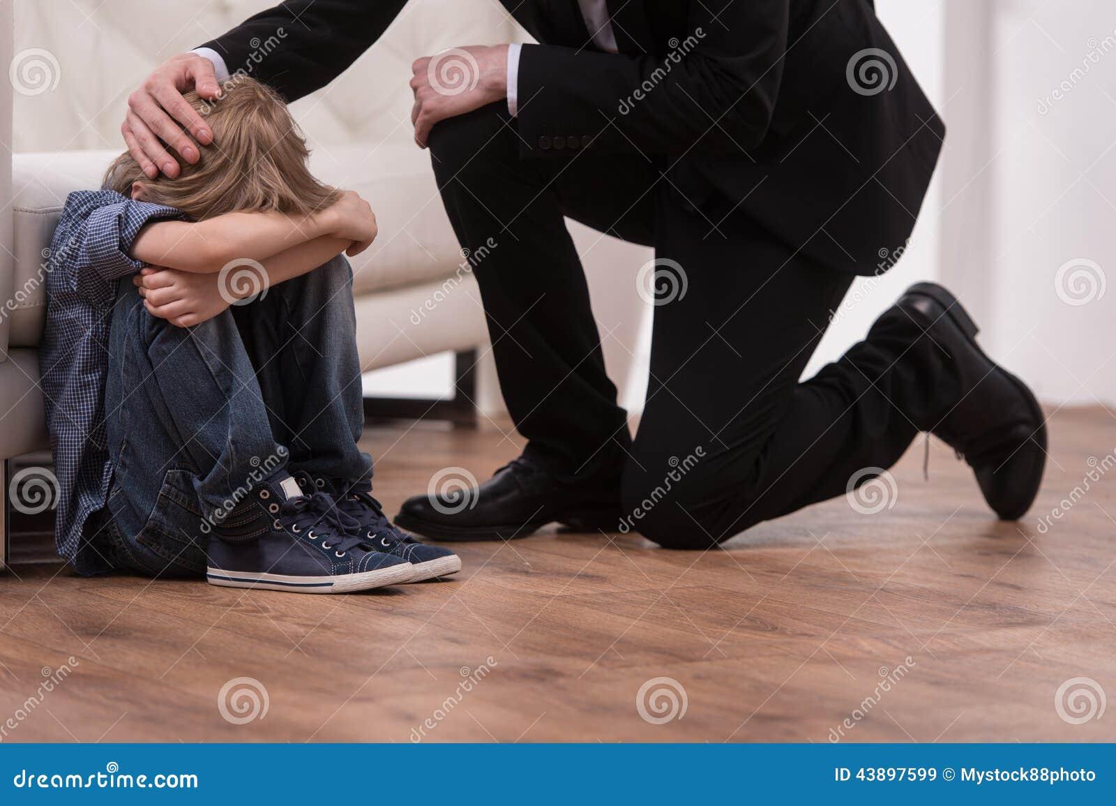 Inginocchiamento del padre e bambino triste di comodità
