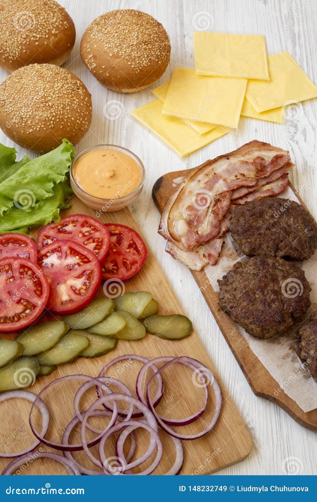 Ingrédients d hamburger sur un fond en bois blanc, vue de côté Plan rapproch?