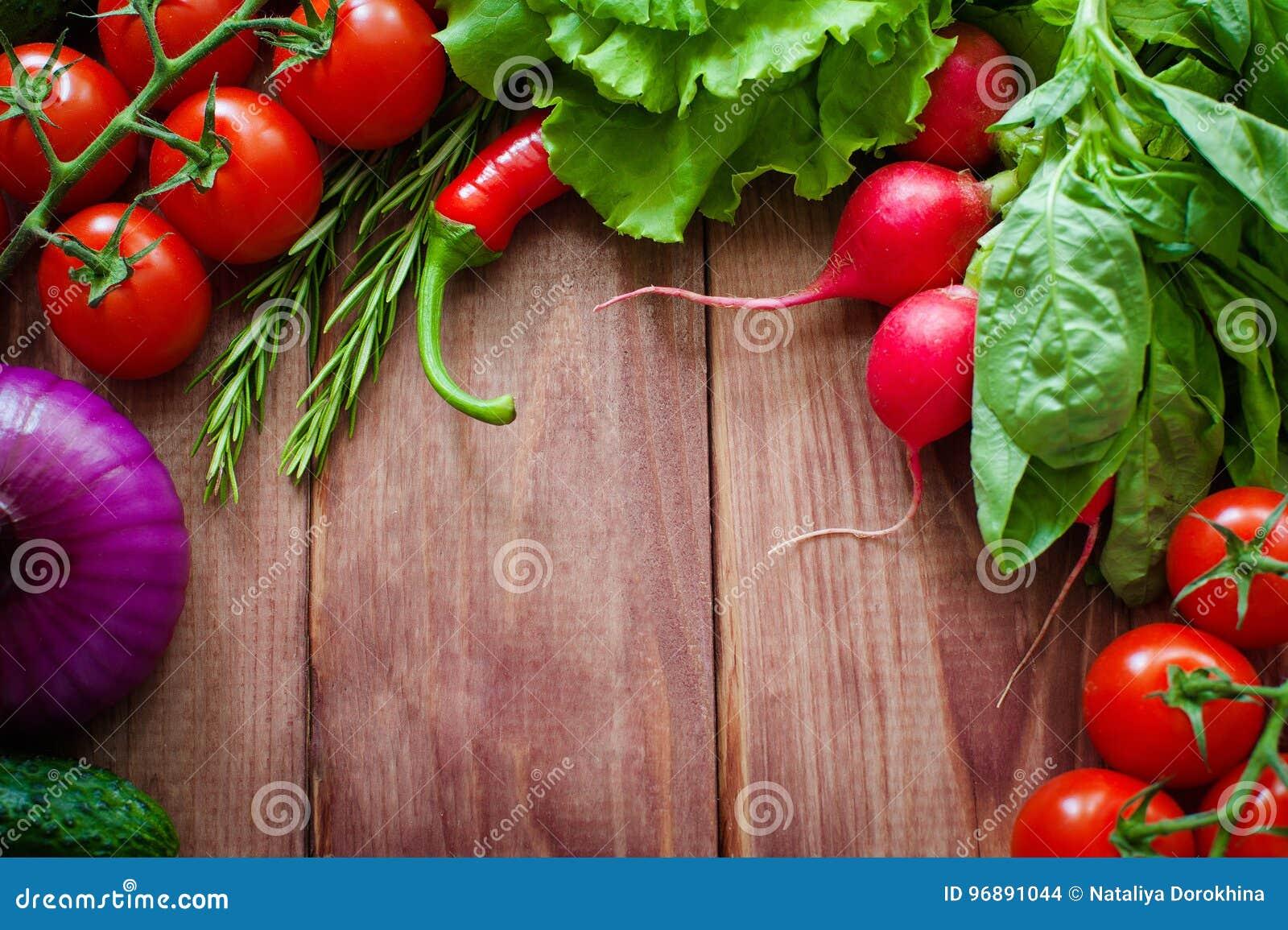 Ingrédients frais pour faire cuire dans l arrangement rustique : Salade, radis, oignon, maïs, tomates, ail, carottes, concombre,