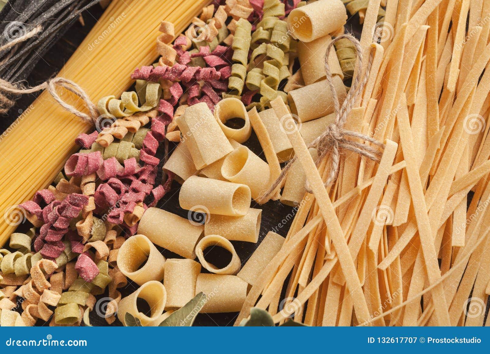 Ingrédients italiens colorés de pâtes et de cuisson sur la table en bois