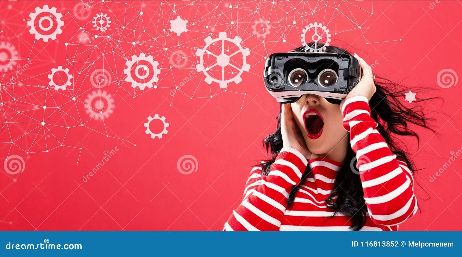 Ingranaggi con la donna che per mezzo di una cuffia avricolare di realtà virtuale