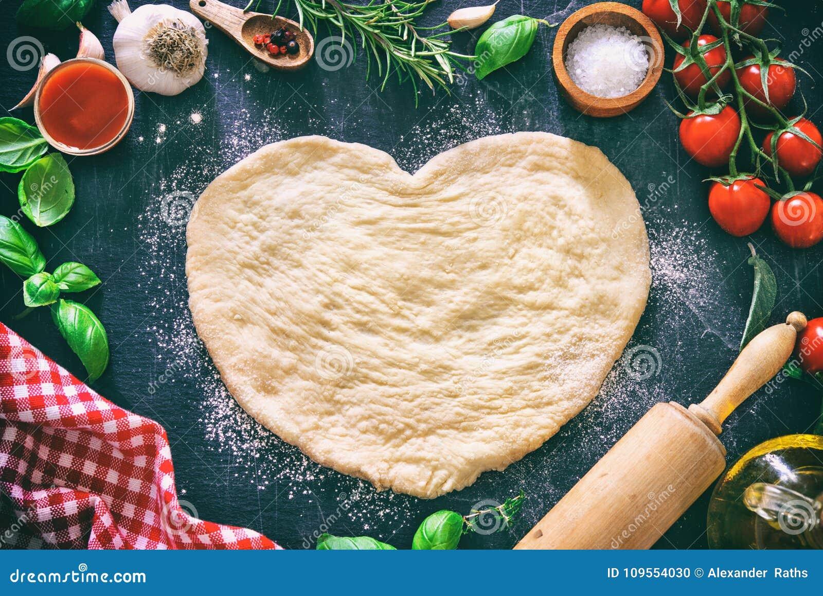Ingredienser för att laga mat pizza eller pasta med deg i hjärtaform