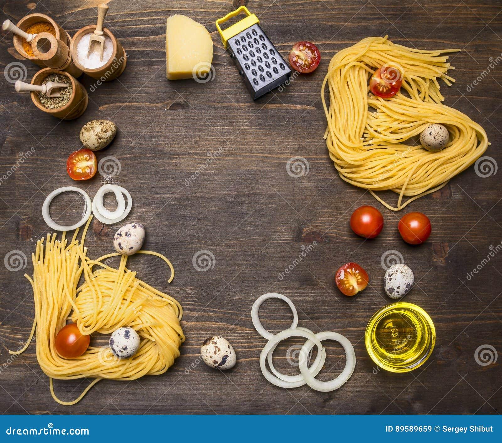 Ingredienser för att laga mat vegetarisk pasta med körsbärsröda tomater, lökar, parmesanost, en variation av lantlig träbackg för