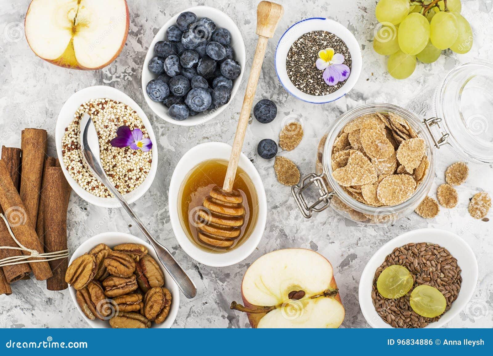 Ingredienser för en sund säsongsbetonad höstfrukost: äpplen druvor, pecannöt, chiafrö, quinoa, linfrö, honung