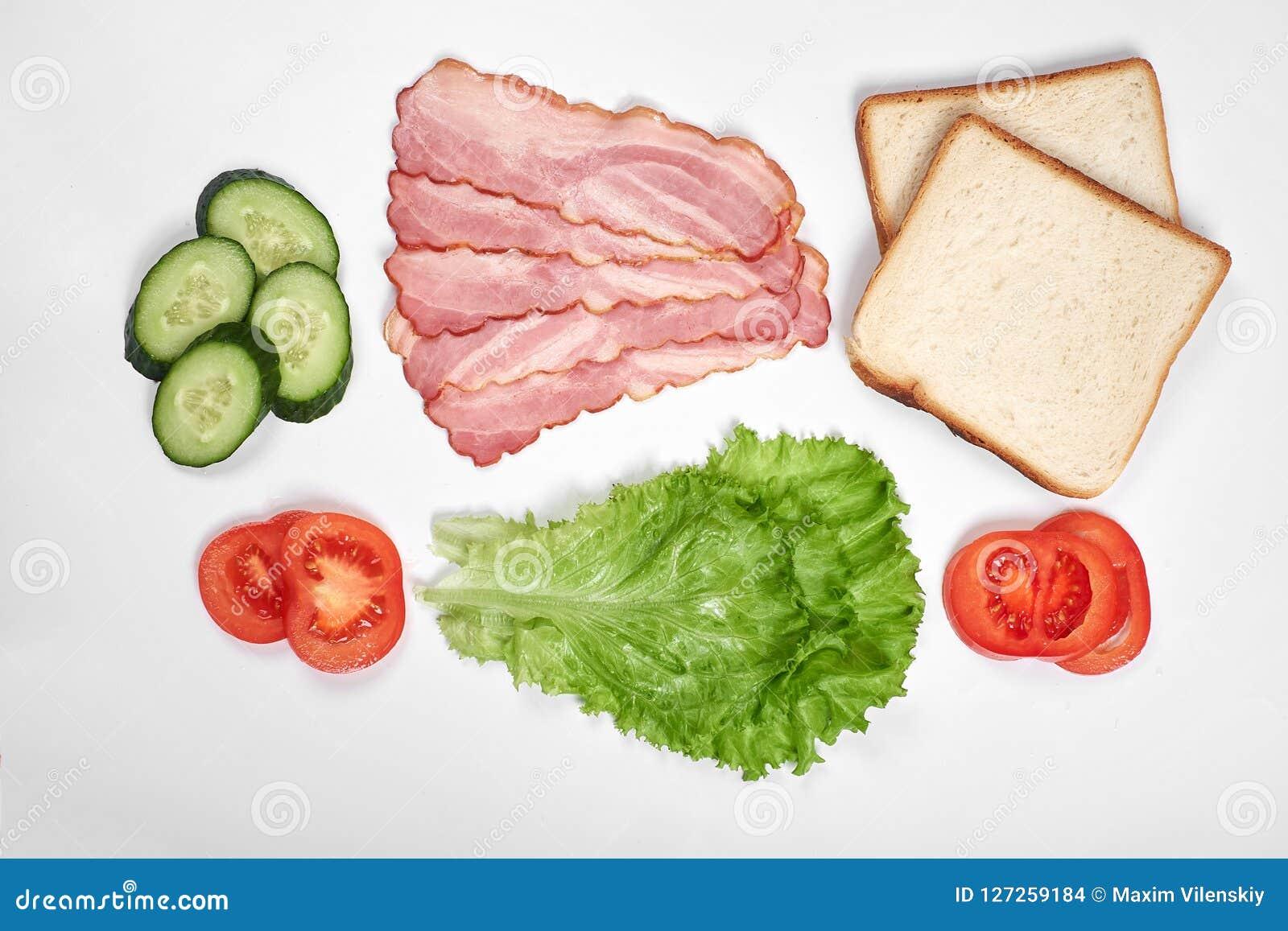Ingredienser för framställning av smörgåsen nya grönsaker, tomater, bröd, becon Isolerat på vit bakgrund, bästa sikt, kopia