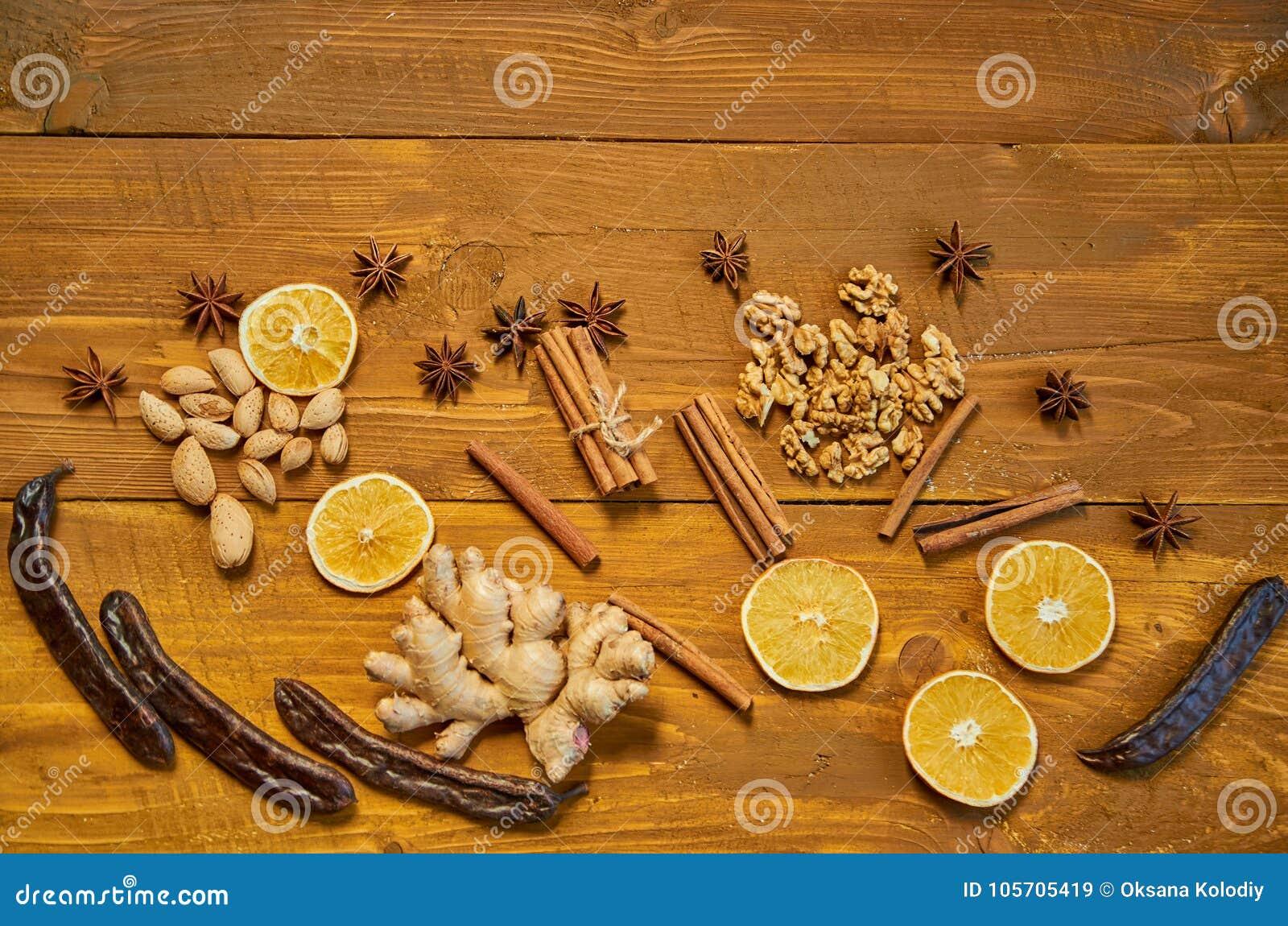 Ingredienser för funderat vin: torkade frukter, apelsin, carob, ingefära, pinnar av kanel, anisstjärnor, muttrar på träbrun bakgr