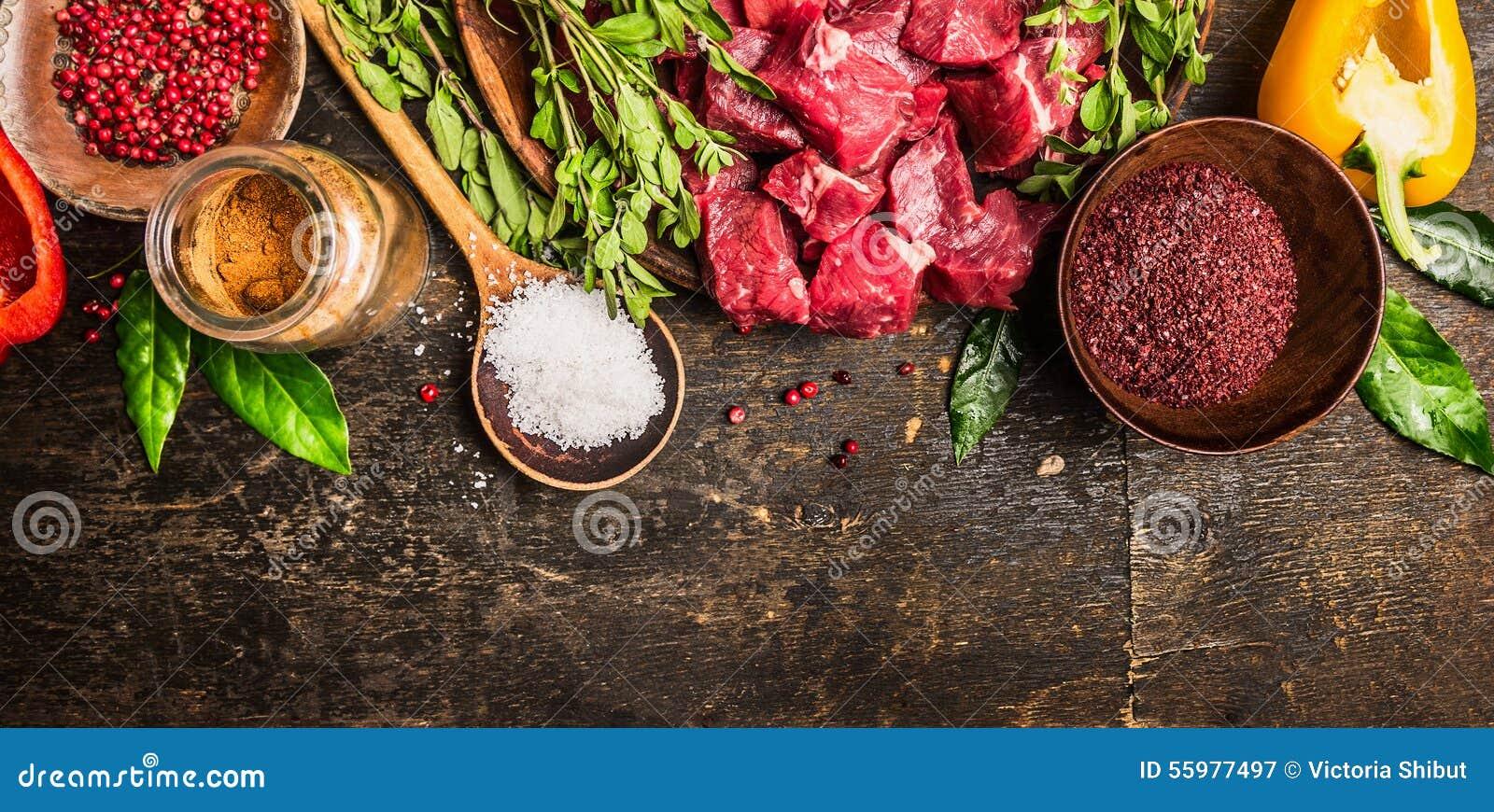 Ingredienser för gulasch- eller ragumatlagning: rått kött, örter, kryddor, grönsaker och sked av salt på lantlig träbakgrund, bäs