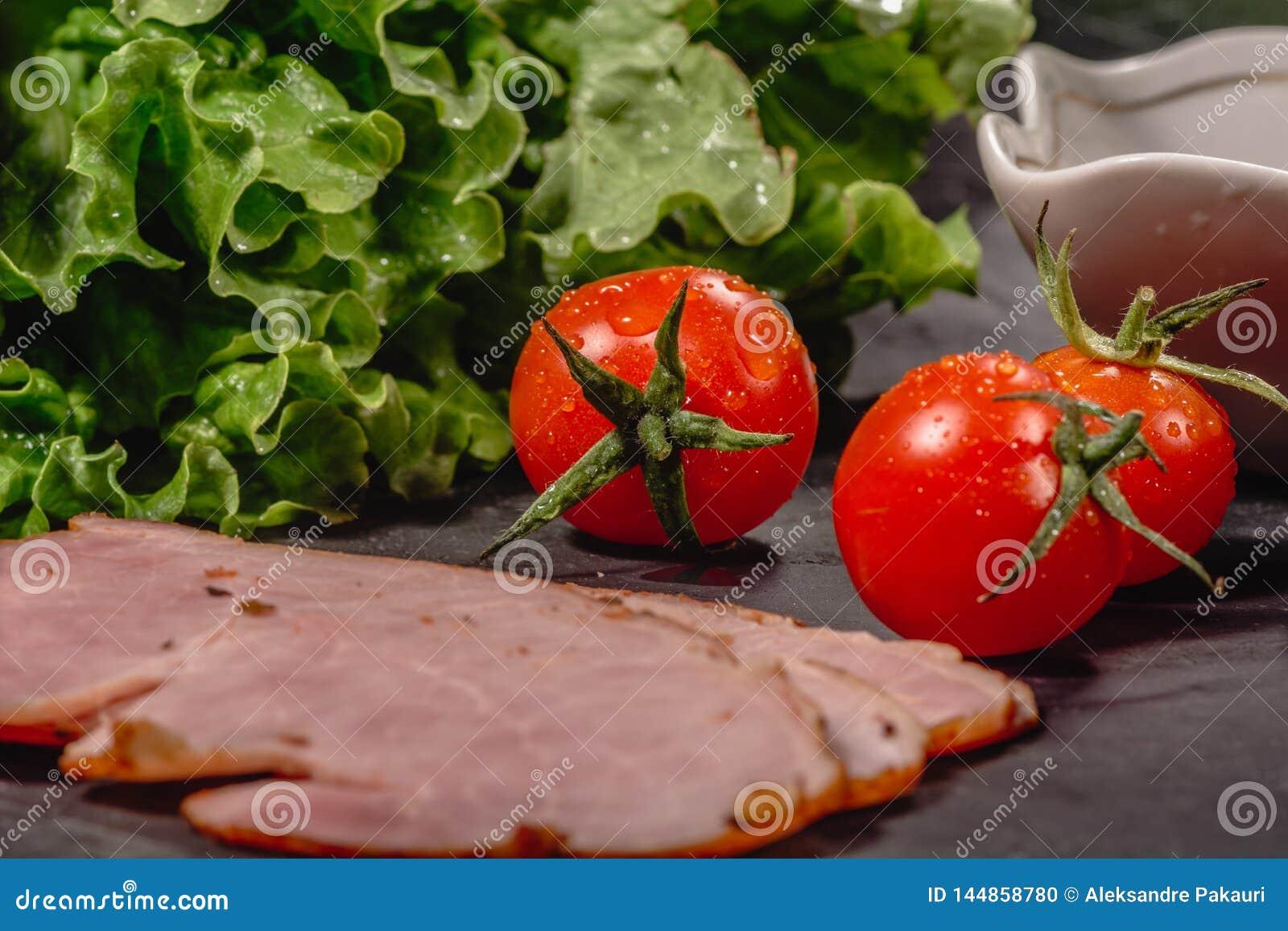 Ingredienser f?r att laga mat italiensk bruschetta p? den m?rka tabellen Italiensk bruschetta med k?rsb?rsr?da tomater, osts?s, s