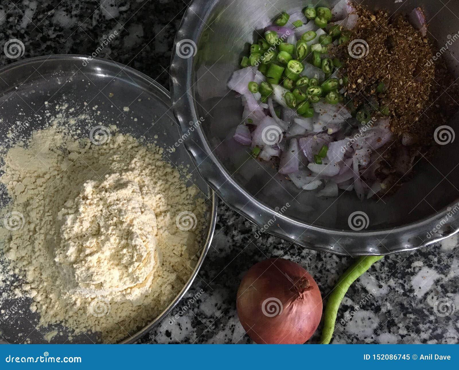 Ingredienser uppställda för kandabhajiOnionen Pakora i monsun Kalyan Maharashtra INDIEN