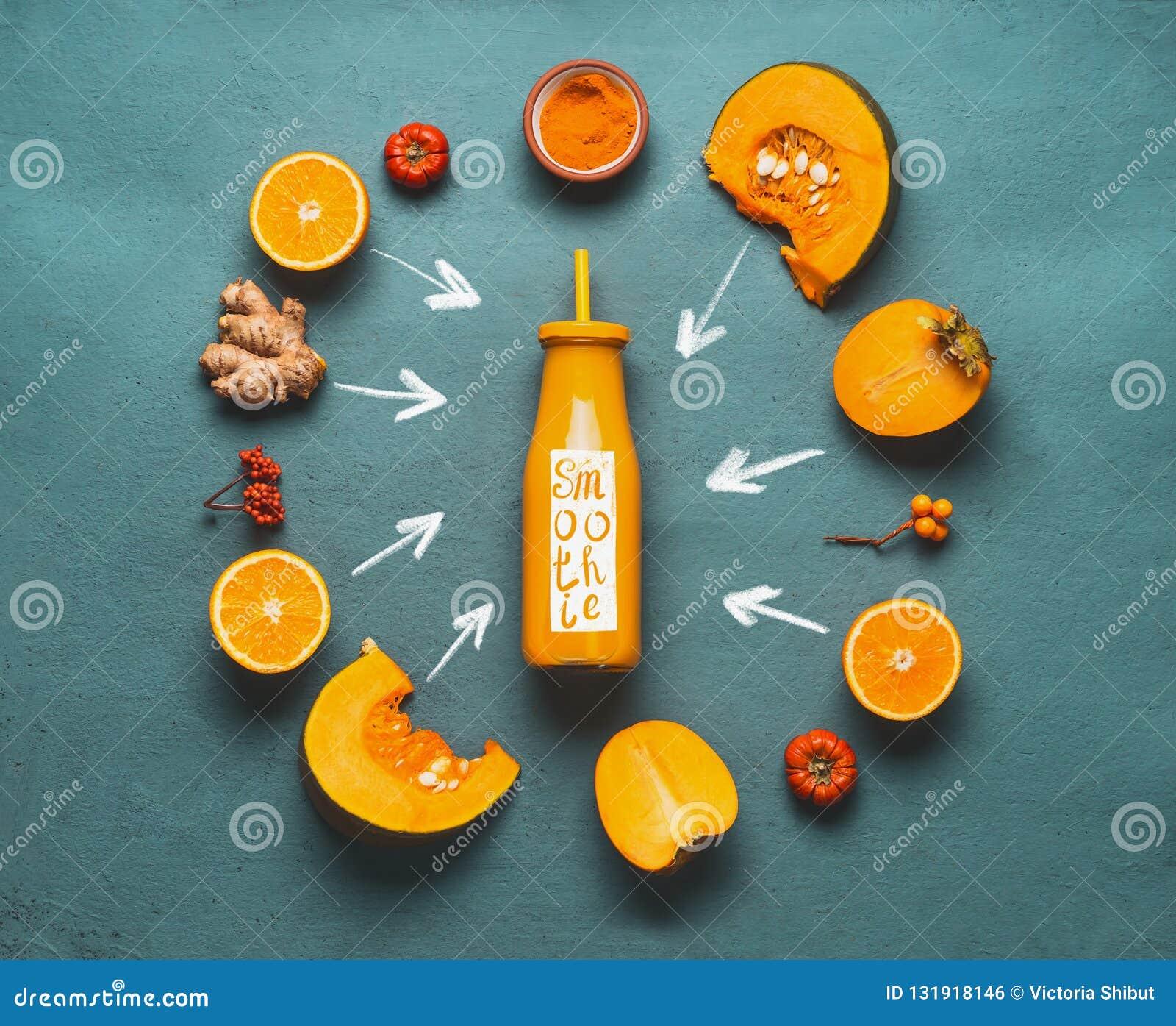 Ingredientes alaranjados do batido: abóbora, caqui, pó alaranjado dos frutos, do gengibre e da cúrcuma em torno da garrafa