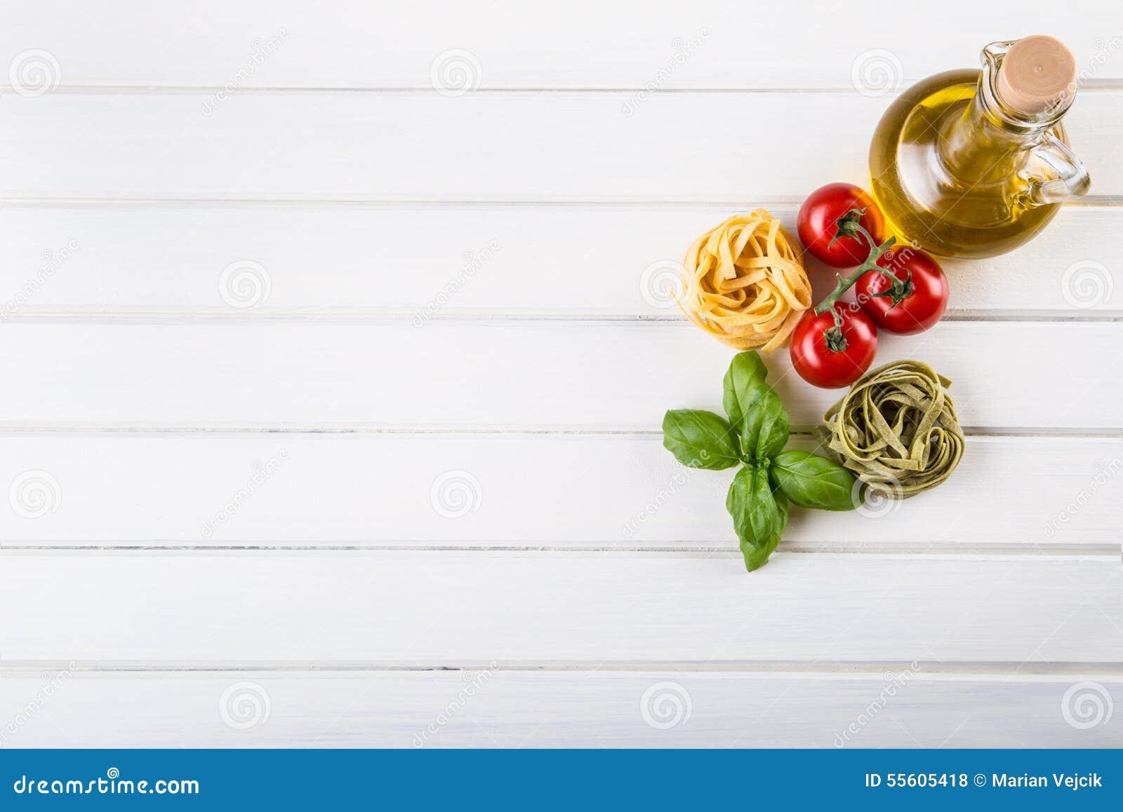 Ingredientes alimentarios italianos y mediterráneos en fondo de madera Pastas de los tomates de cereza, hojas de la albahaca y ga