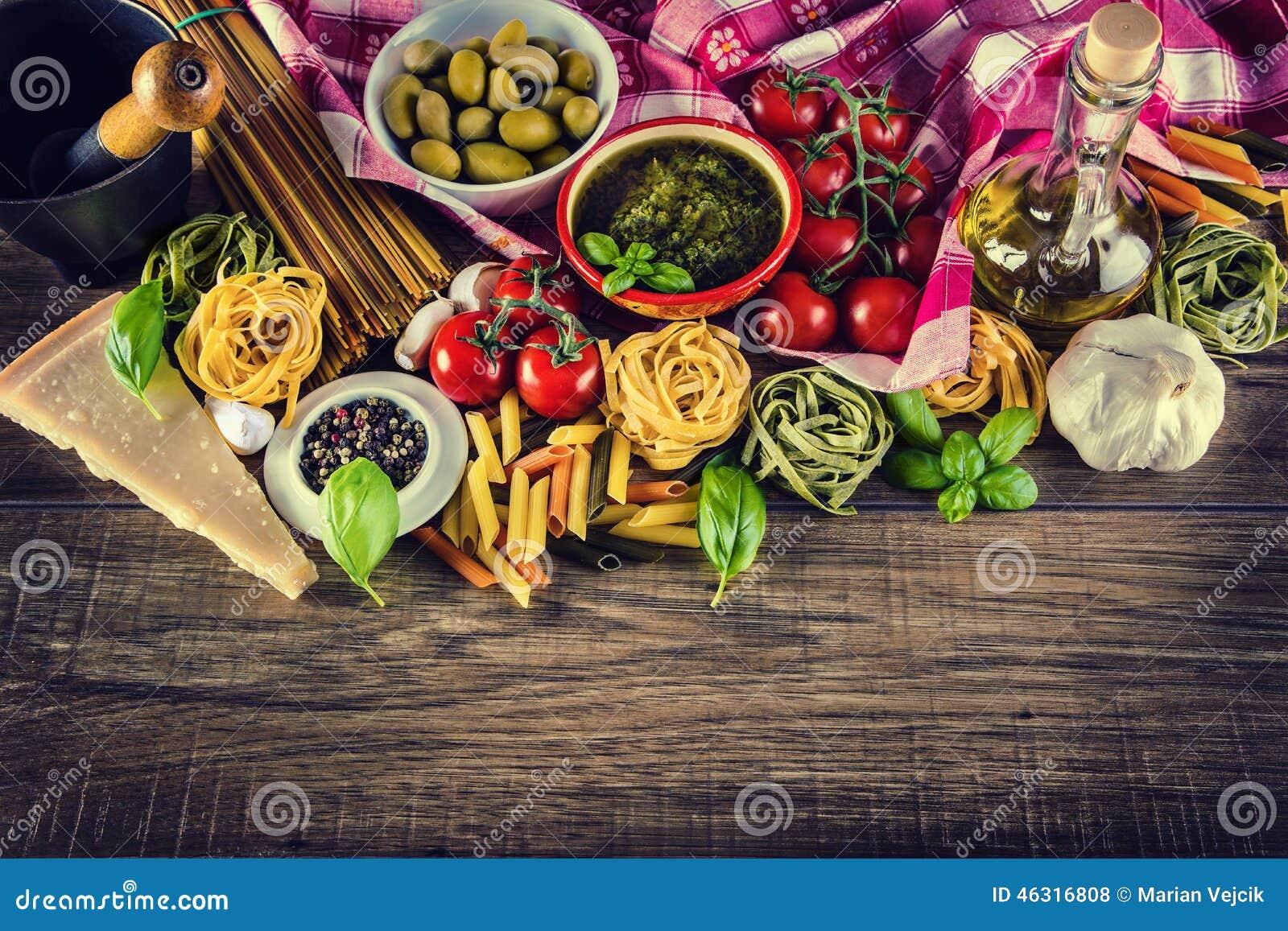 Ingredientes de alimento italianos e mediterrâneos no fundo de madeira velho