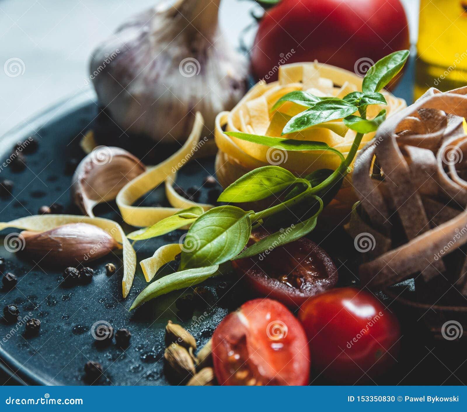 Ingredientes de alimento italianos em uma placa cerâmica