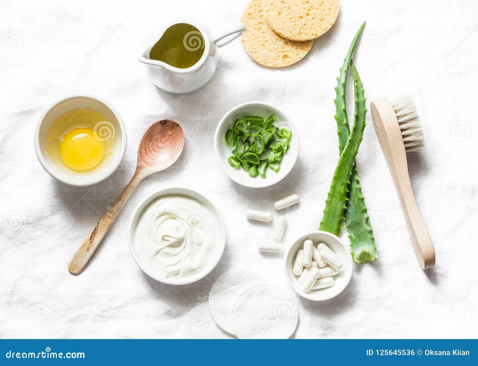 Ingredientes de la mascarilla del áloe - áloe, yogur, huevo, aceite de oliva y accesorios de la belleza en el fondo ligero, visió