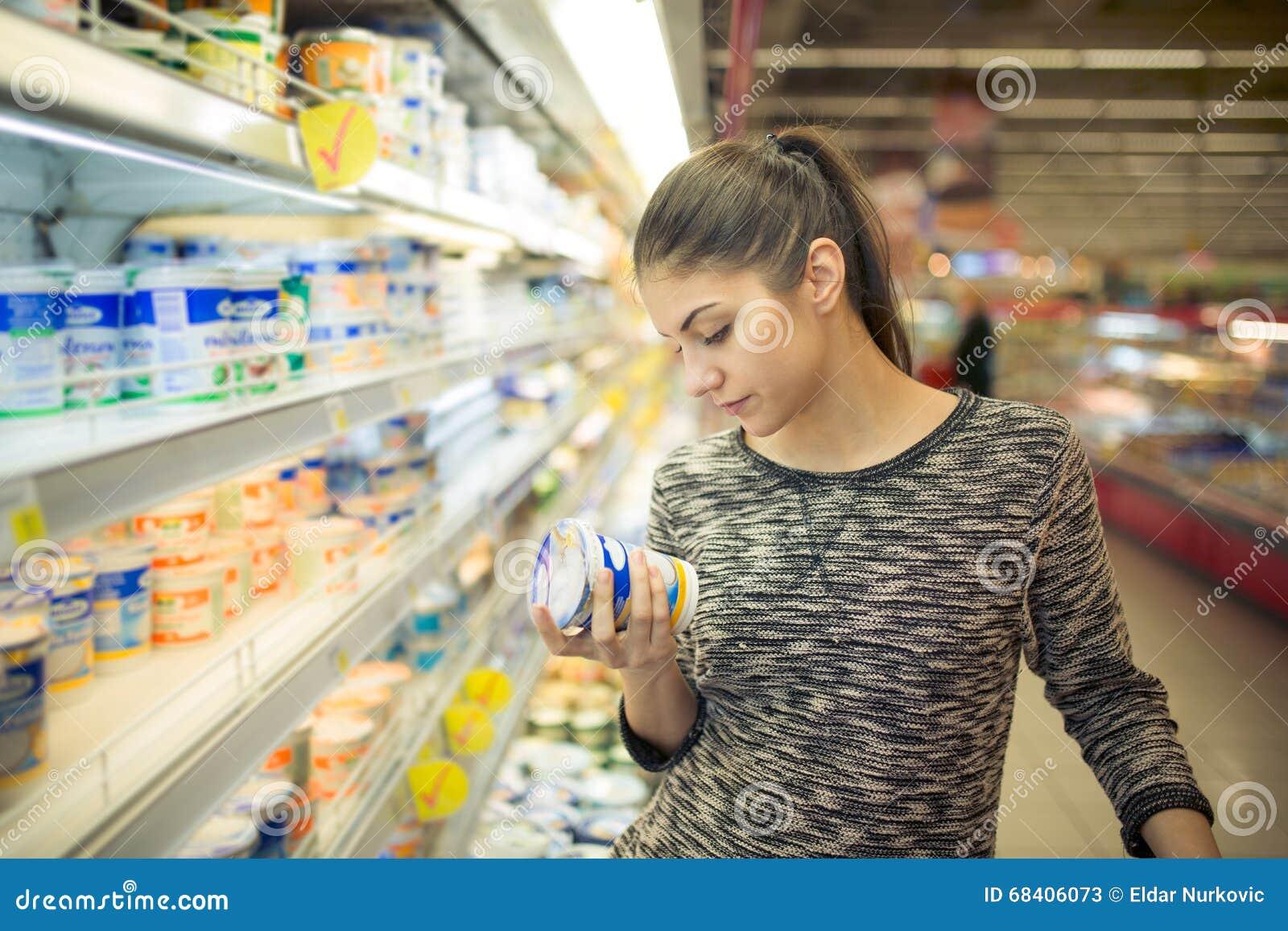 Ingredientes, declaração ou data de validade da leitura da jovem mulher em um produto do diário antes de comprá-lo Nutrição curio