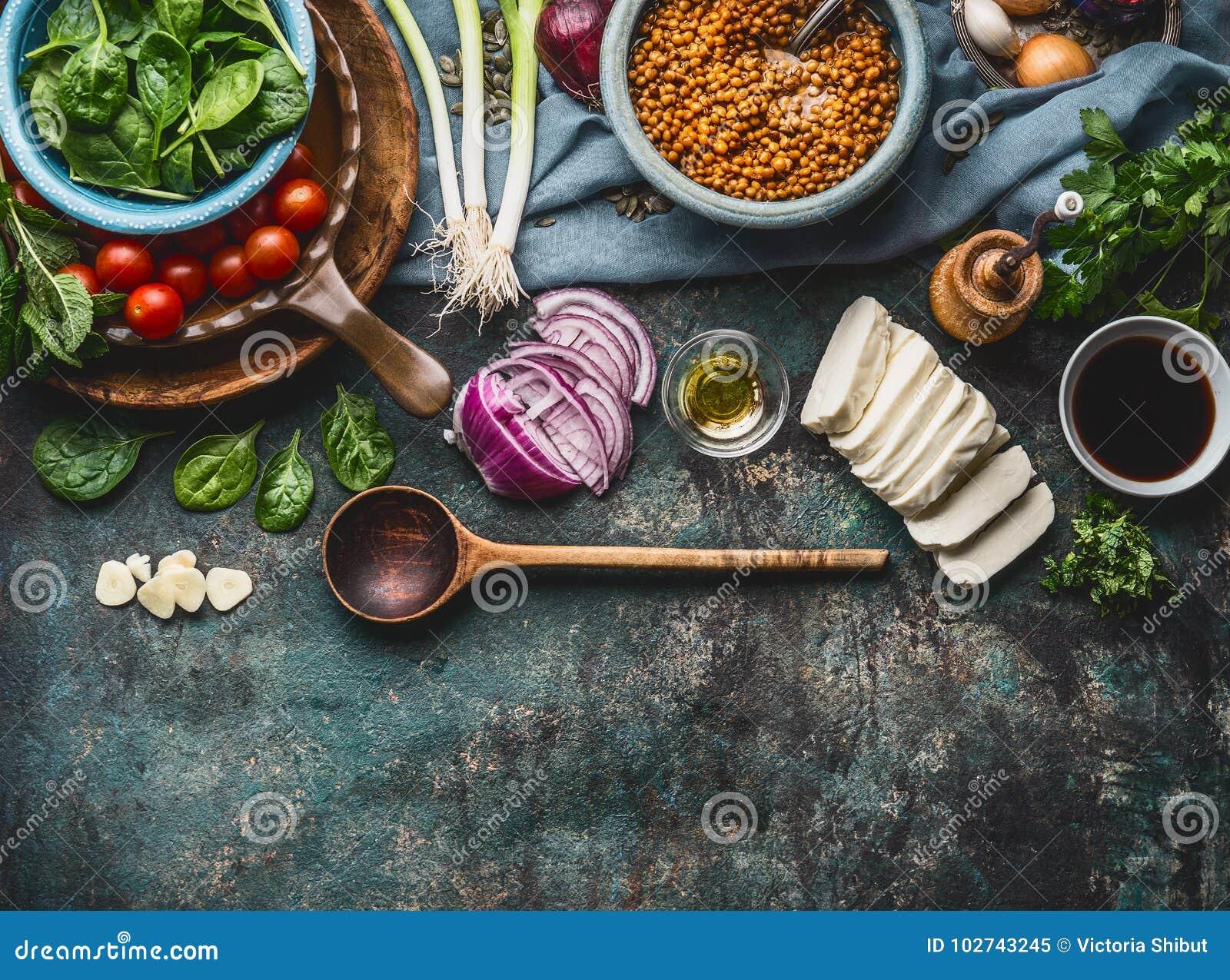 Ingredientes do vegetariano para pratos saborosos da lentilha no fundo rústico da mesa de cozinha com cozimento da colher e dos u