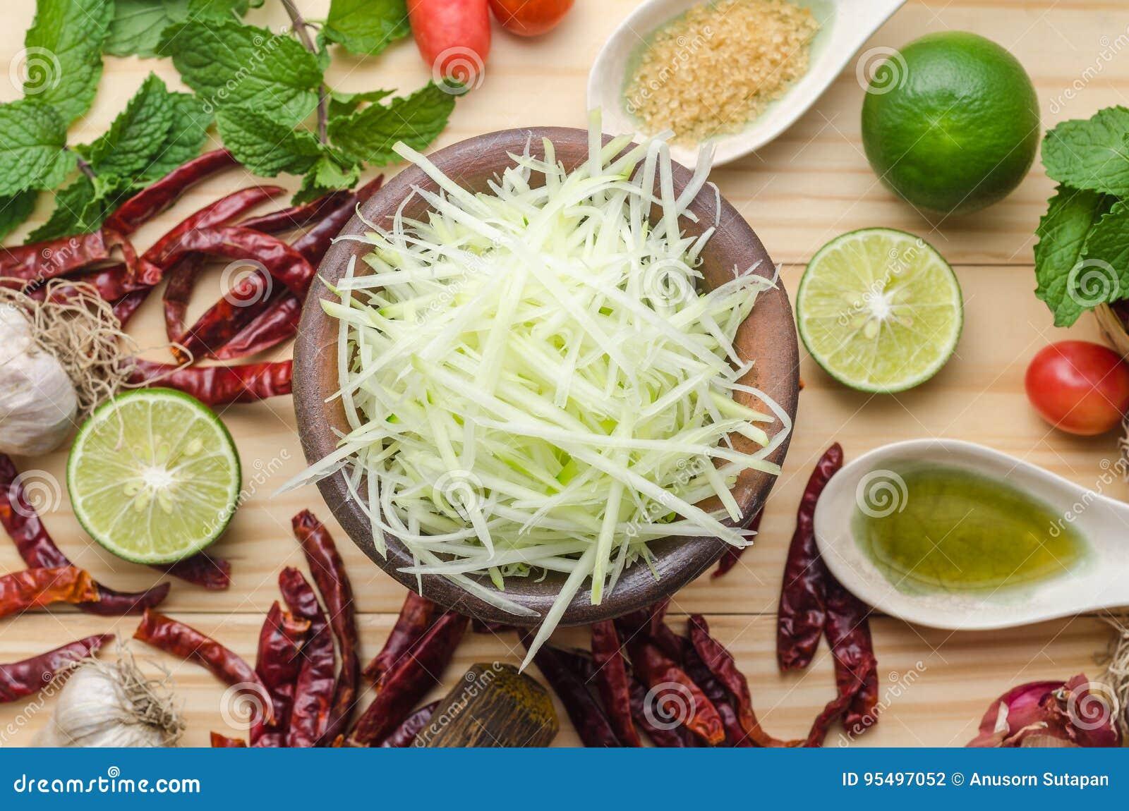 Ingredientes para hacer la ensalada de la papaya en una tabla de madera Sistema de Th